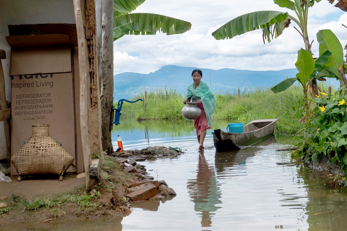 Muktarei Oinam wades through the flooded front yard of her home in the village of Thanga in the Loktak area of Manipur.