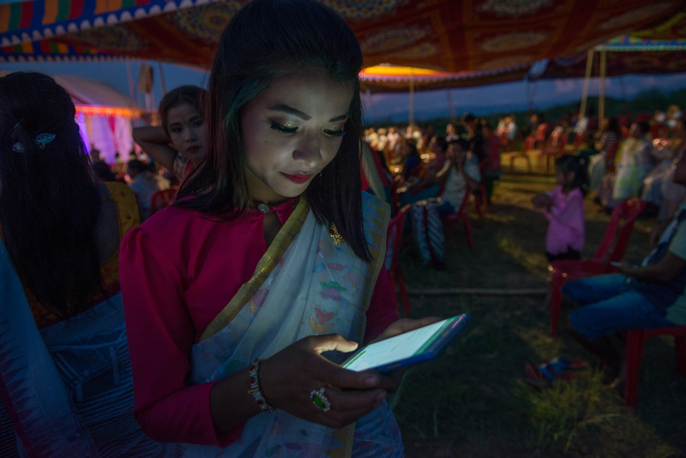 Echan, a teenage performer at the Loktak Day festivities held in the village of Thanga, Manipur uses her phone. The younger generation in communities surrounding Loktak is moving away from the traditional livelihood of fishing because making a living from fishing has become challenging.