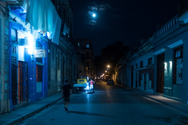 A couple try to fix their vehicle in the moonlight in La Habana