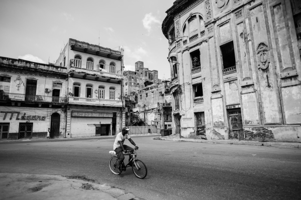A man having a bike ride through the dilapidated buildings just behind the Capitolio, La Habana