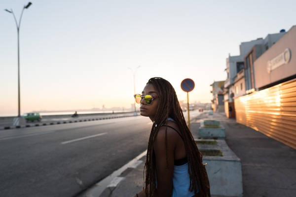 A young girl waits for the bus at El Malecón, La Habana