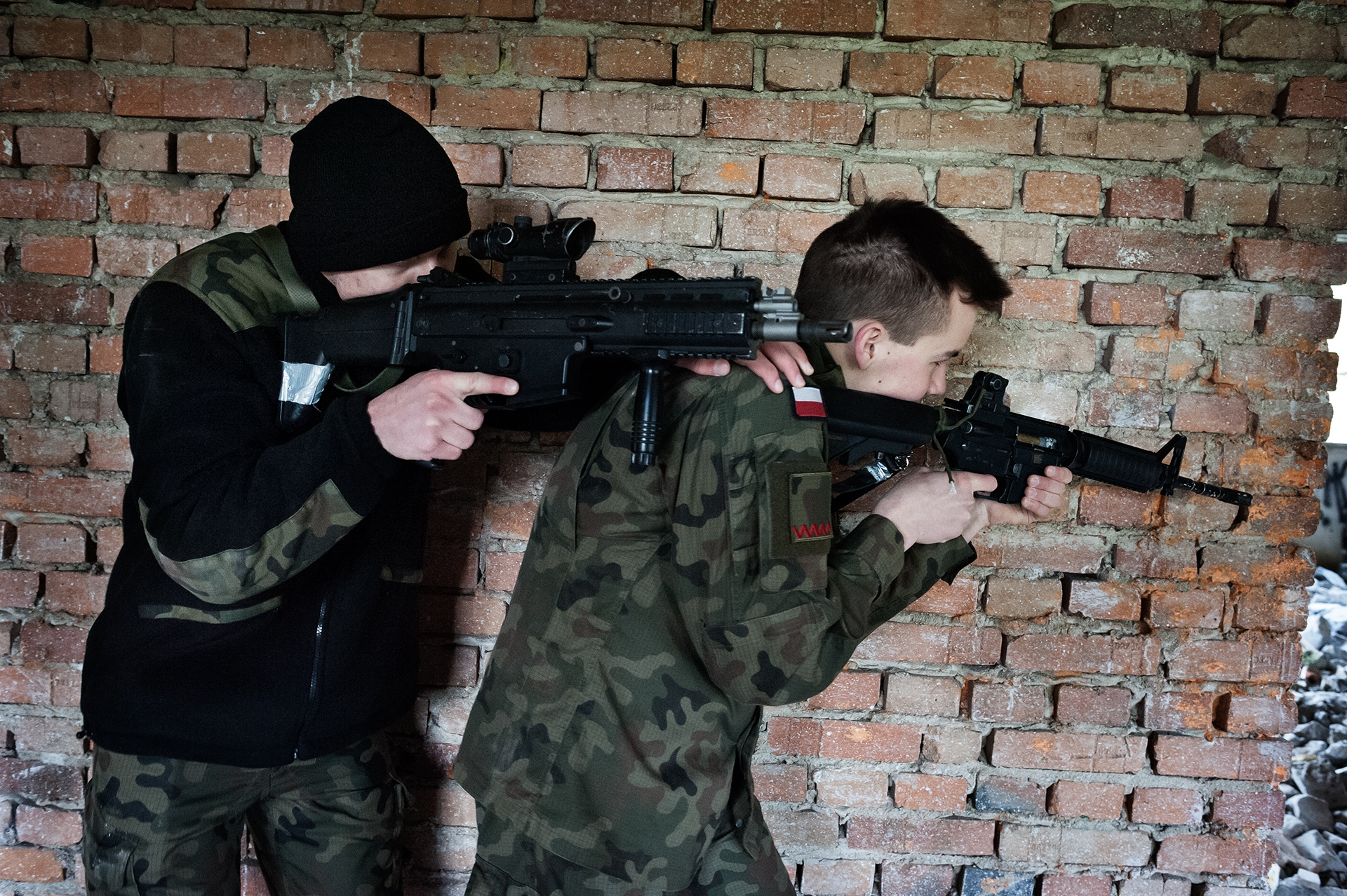 """Students (16-19 years old) learn combat tactics in urban areas under the supervision of a paramilitary organization (Unit 3060). Skarbimierz/Brzeg 2017 """"Children will play war anyway. When they are in a sandbox for example, they would play with sticks if they don't have toy weapons, so it is obvious they have this need."""" (Malgorzata Baranowska, the history professor responsible for military classes at school)."""