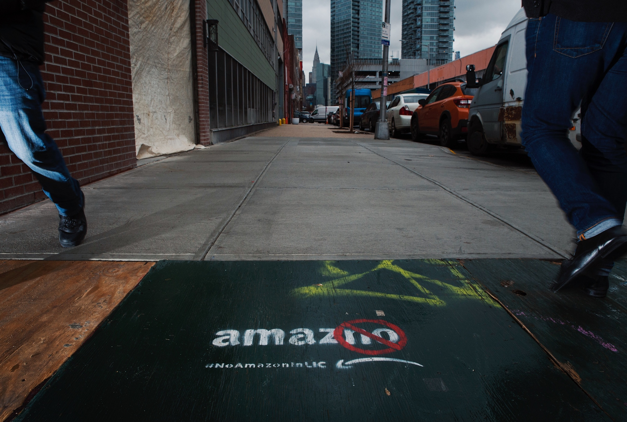 "Pedestrians pass by a ""AmazNO -- #noAmazoninLIC"" sign on 5-98 46th Avenue, Long Island City, NY, along 46th Avenue on November 26, 2018."