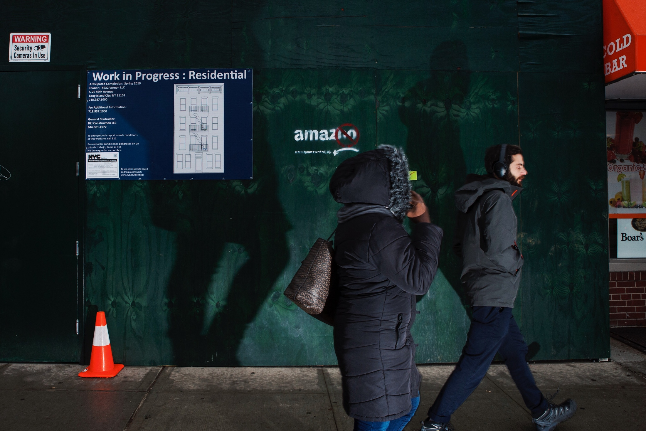 "Pedestrians pass by a ""AmazNO -- #noAmazoninLIC"" sign on 5-98 46th Avenue, Long Island City, NY, along Vernon Blvd on November 26, 2018."