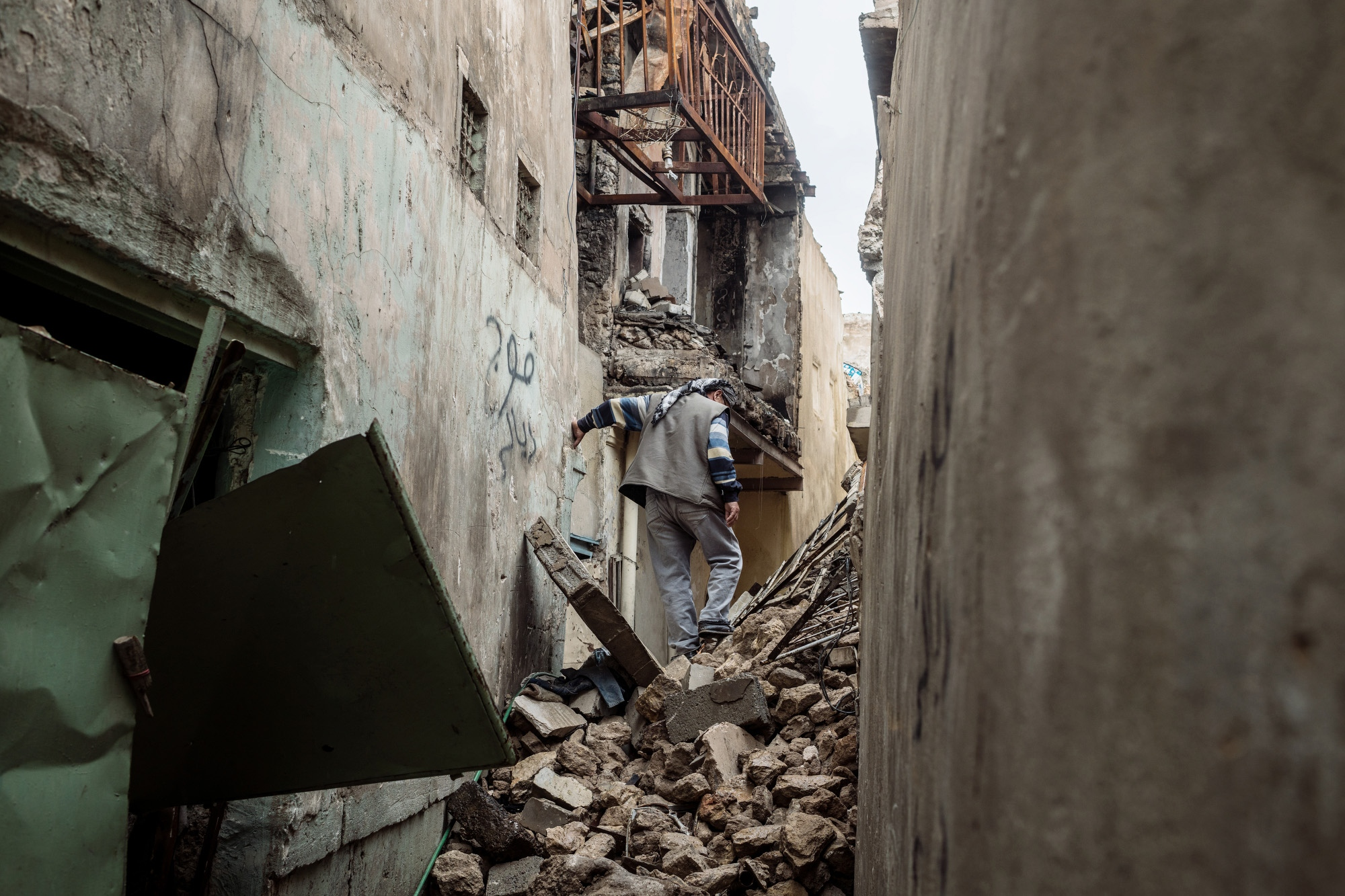 MOSUL 20180413 A man climbs through debris and rubble in an alley of Old Mosul, much of which was destroyed by coalition airstrikes during the liberation from ISIS. Photo: Vilhelm Stokstad / Kontinent