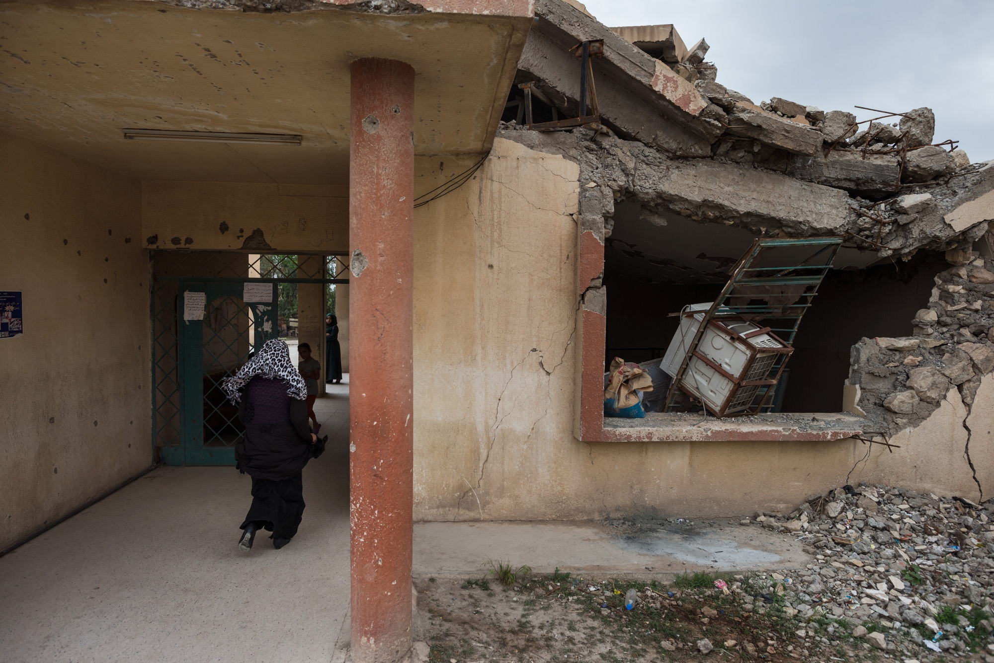 MOSUL 20180412 A teacher enters the Risala girls school in West Mosul. The school is one of few open in Mosuls old town, which was subject to the heaviest fighting during the offensive against Daesh. Photo: Vilhelm Stokstad / Kontinent
