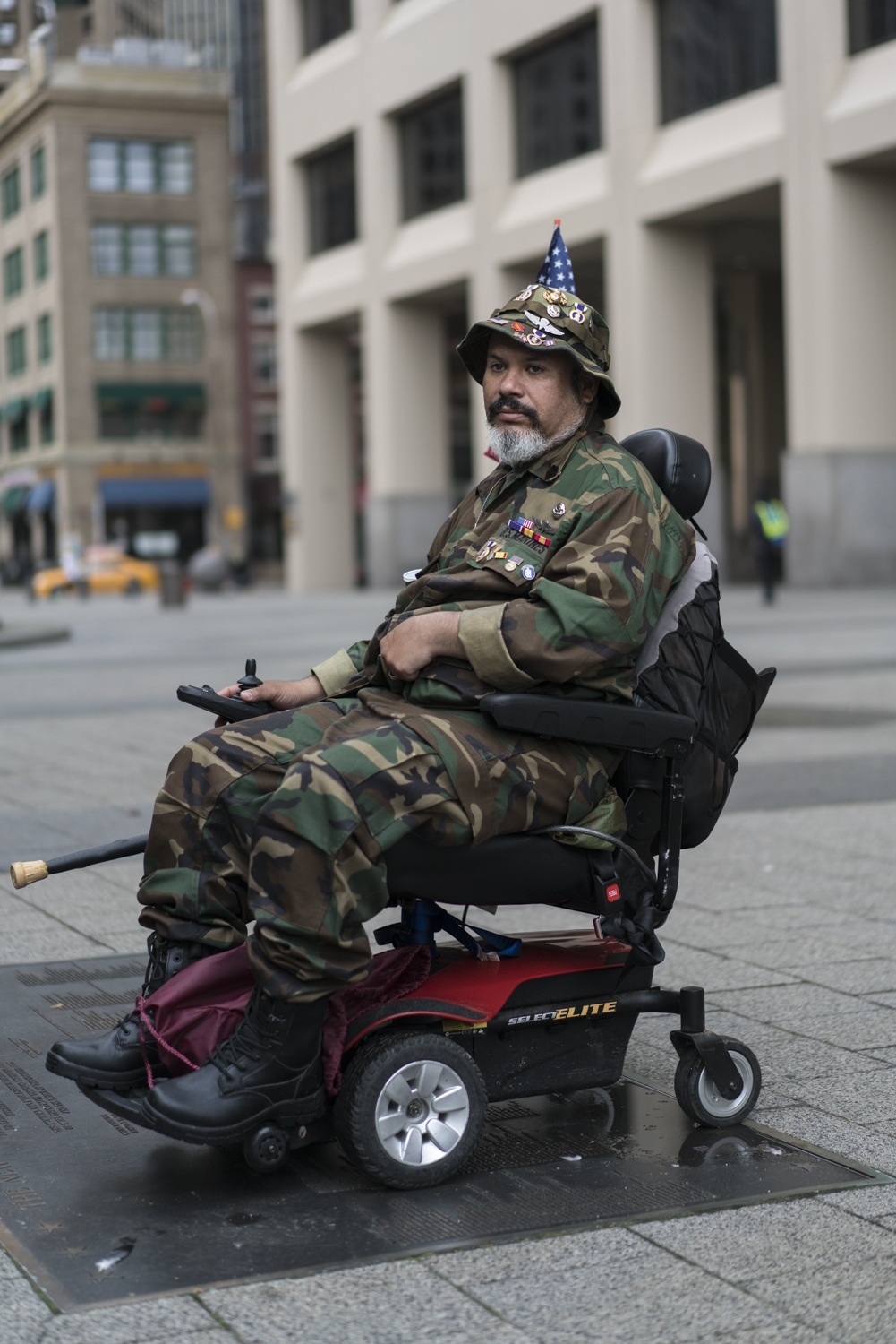 Afghanistan Marine Veteran Eudes Garcia pays tribute on Memorial Day. Shot by a sniper in Fallujah in 2006, Garcia is restrained to a motorized wheelchair. New York City, 2017.