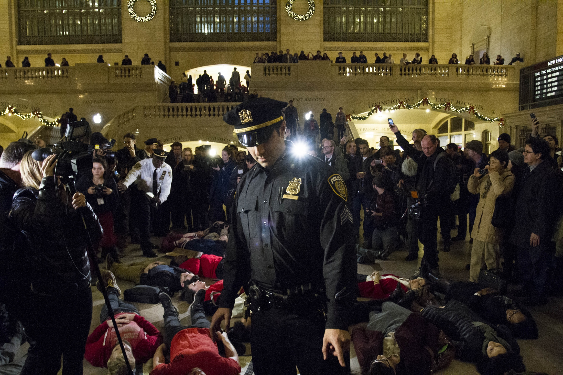 "A policeman addresses a protester participating the Grand Central ""Die-In"" the day the Grand Jury decision to not indict Eric Garner's killer, Daniel Pantaleo was released, Dec. 3, 2014."