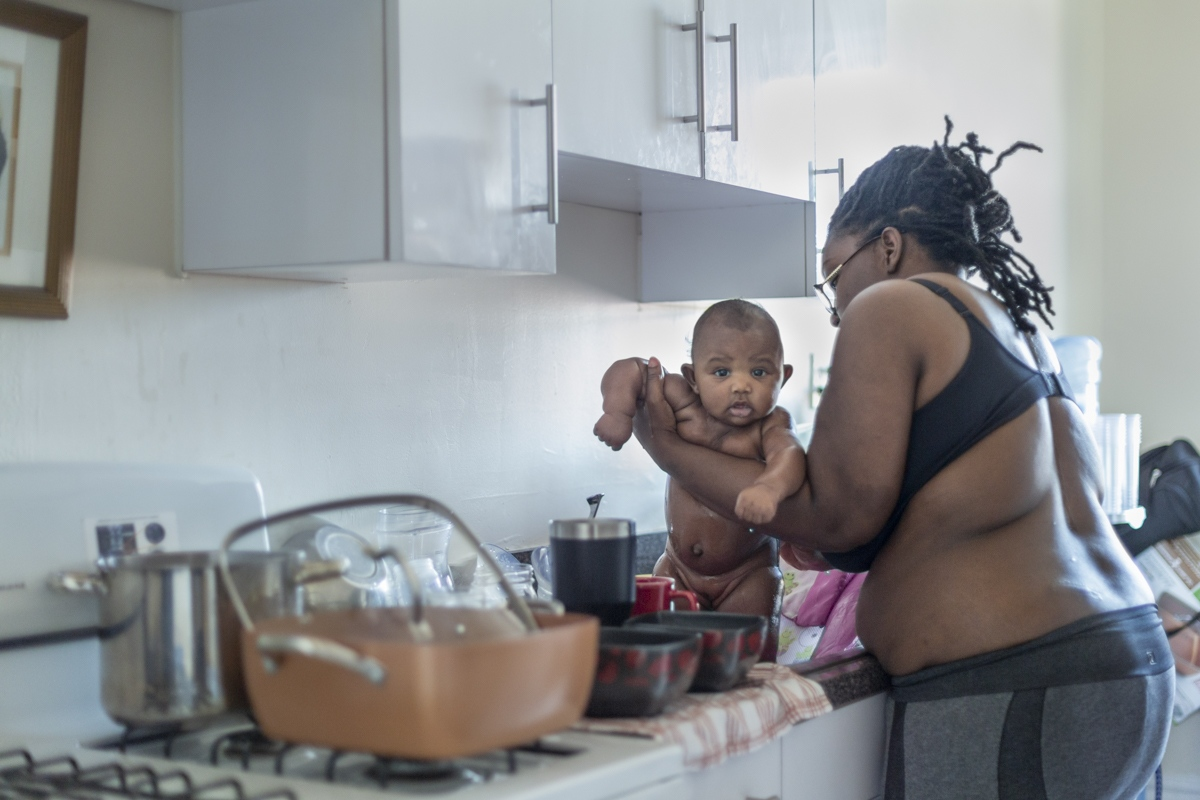 After changing Abigail's diaper, Samantha cleans up her thirteen-weeks-old daughter in the kitchen sink on May 11, 2018.