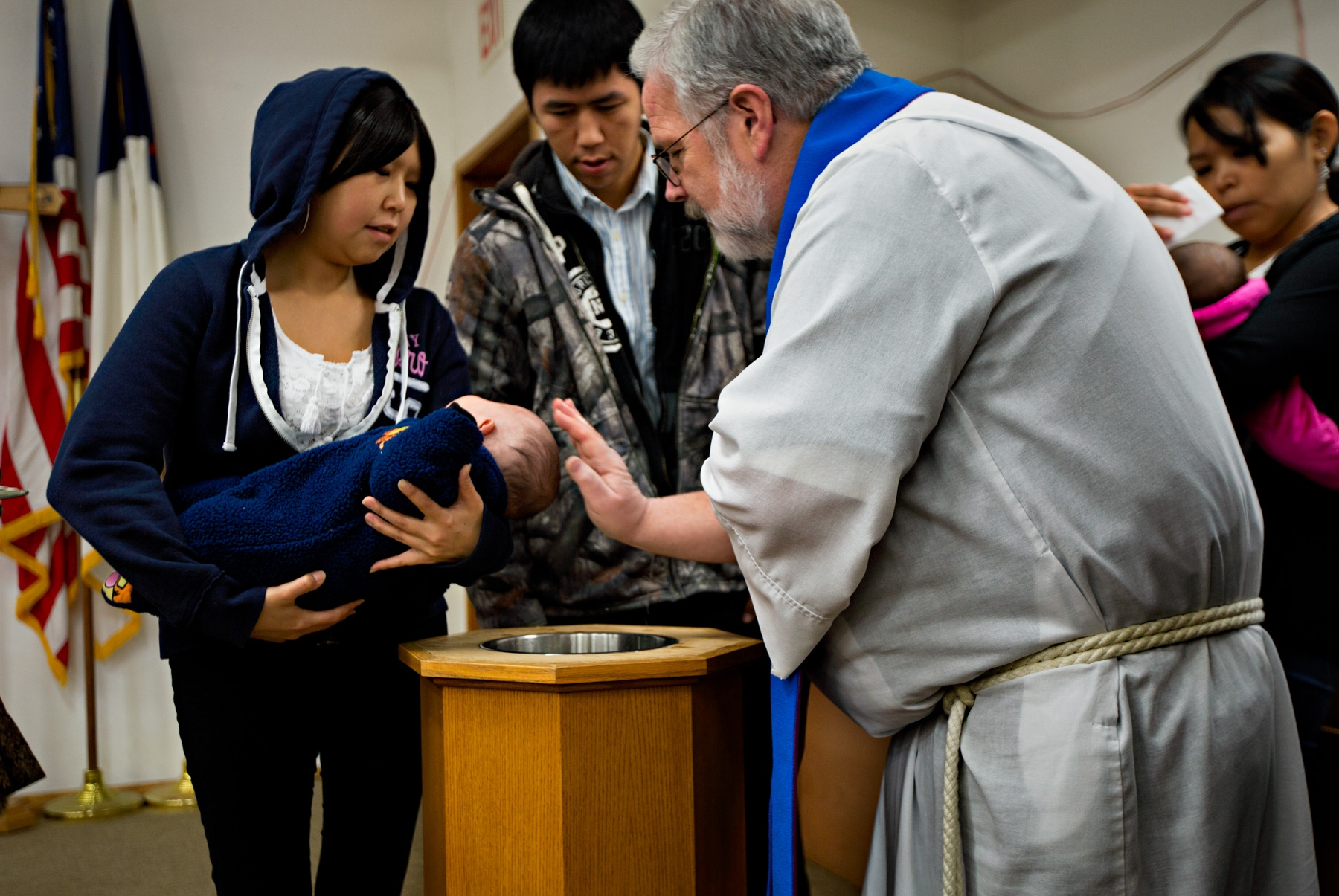 Although most residents of Shishmaref are officially members of the Lutheran Church (the only church in the village), they also observe and respect their traditional Eskimo practices and beliefs. During the Sunday service, Pastor Marvin Jonasen conducts baptism for new parents.