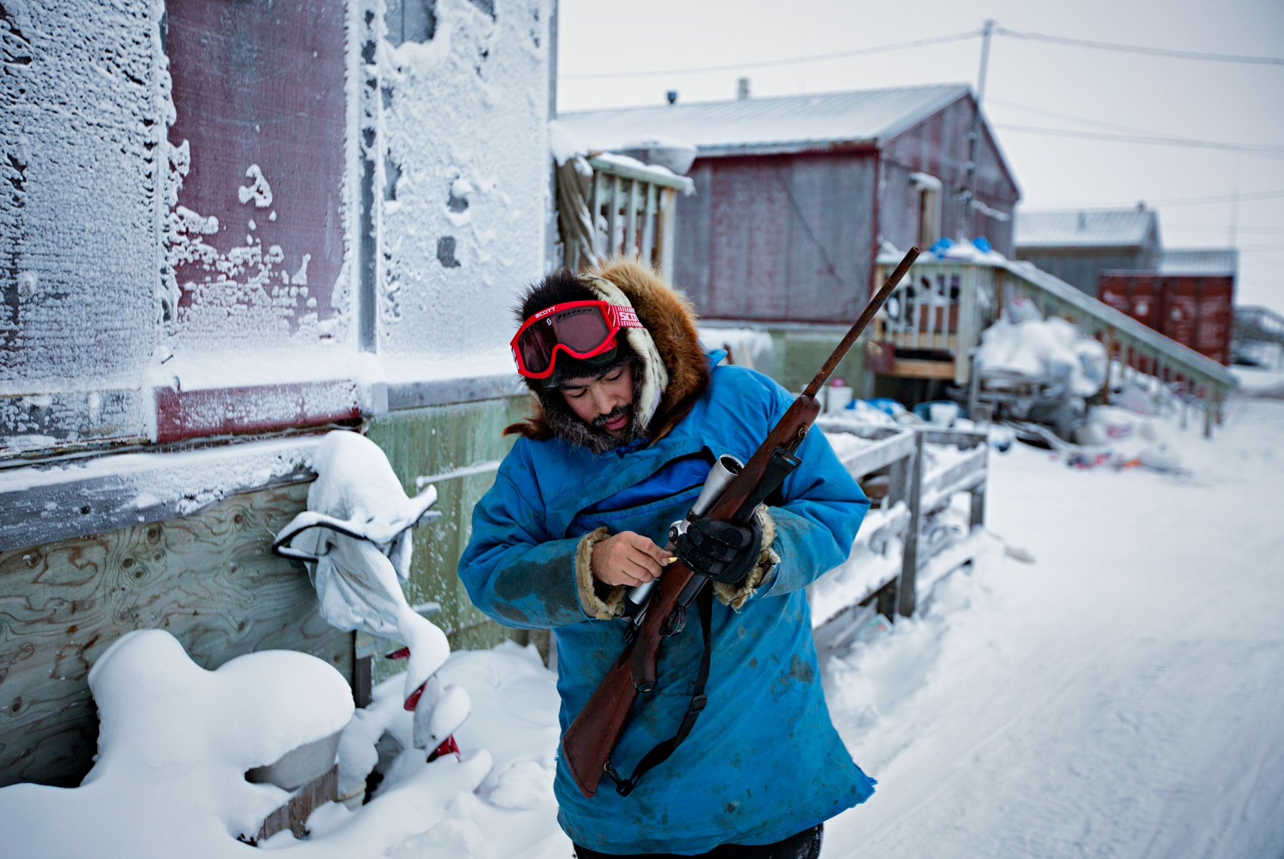 Fred Weyiouanna, 32 years old, and a life long resident loads his Ruger 77 rifle that he uses to hunt caribou. Caribou meat is a major source of food for residents of Shishmaref.
