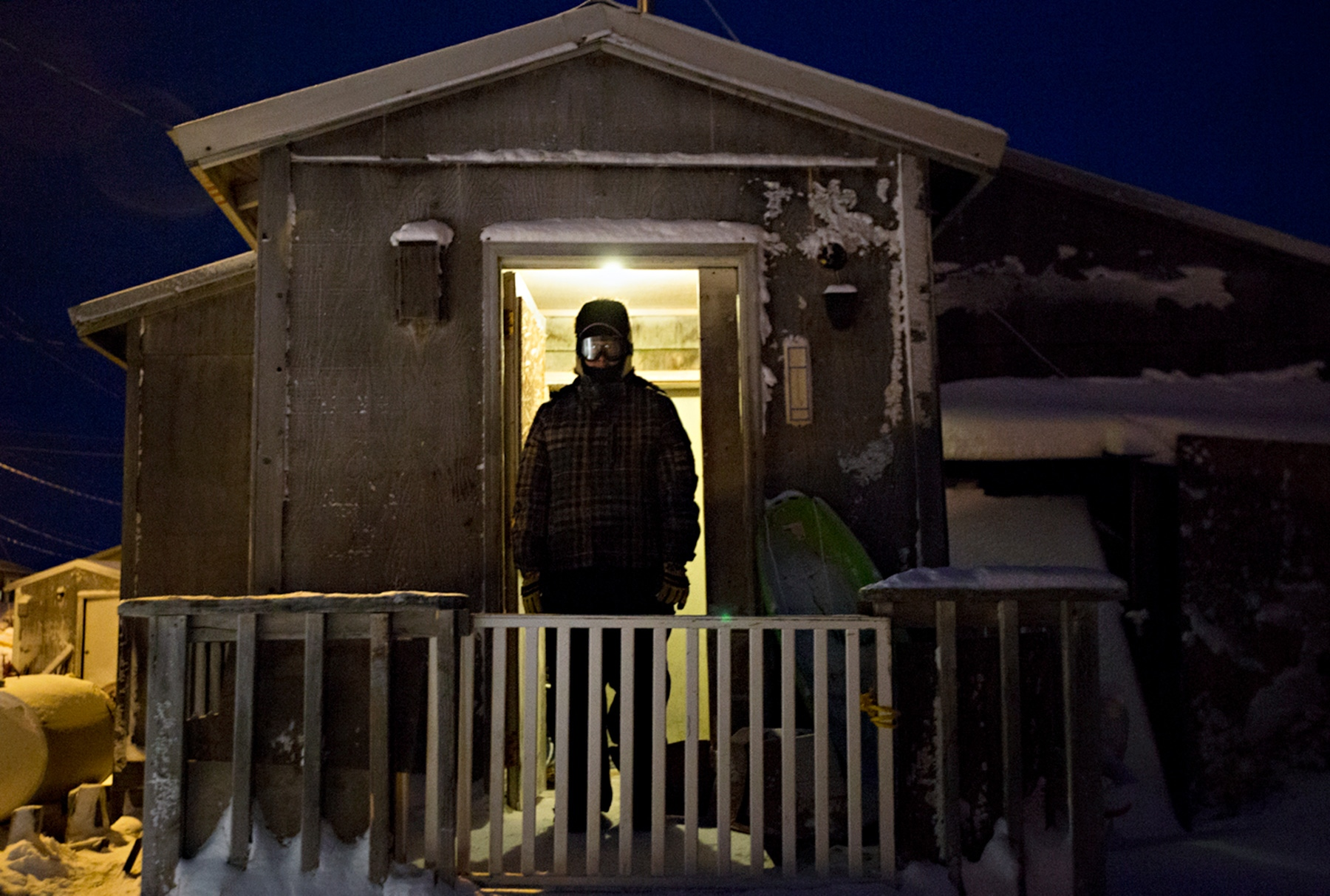 Justin Eningowuk, 27 years old, waits for his snow machine to warm up on a frigid morning before heading out to work.