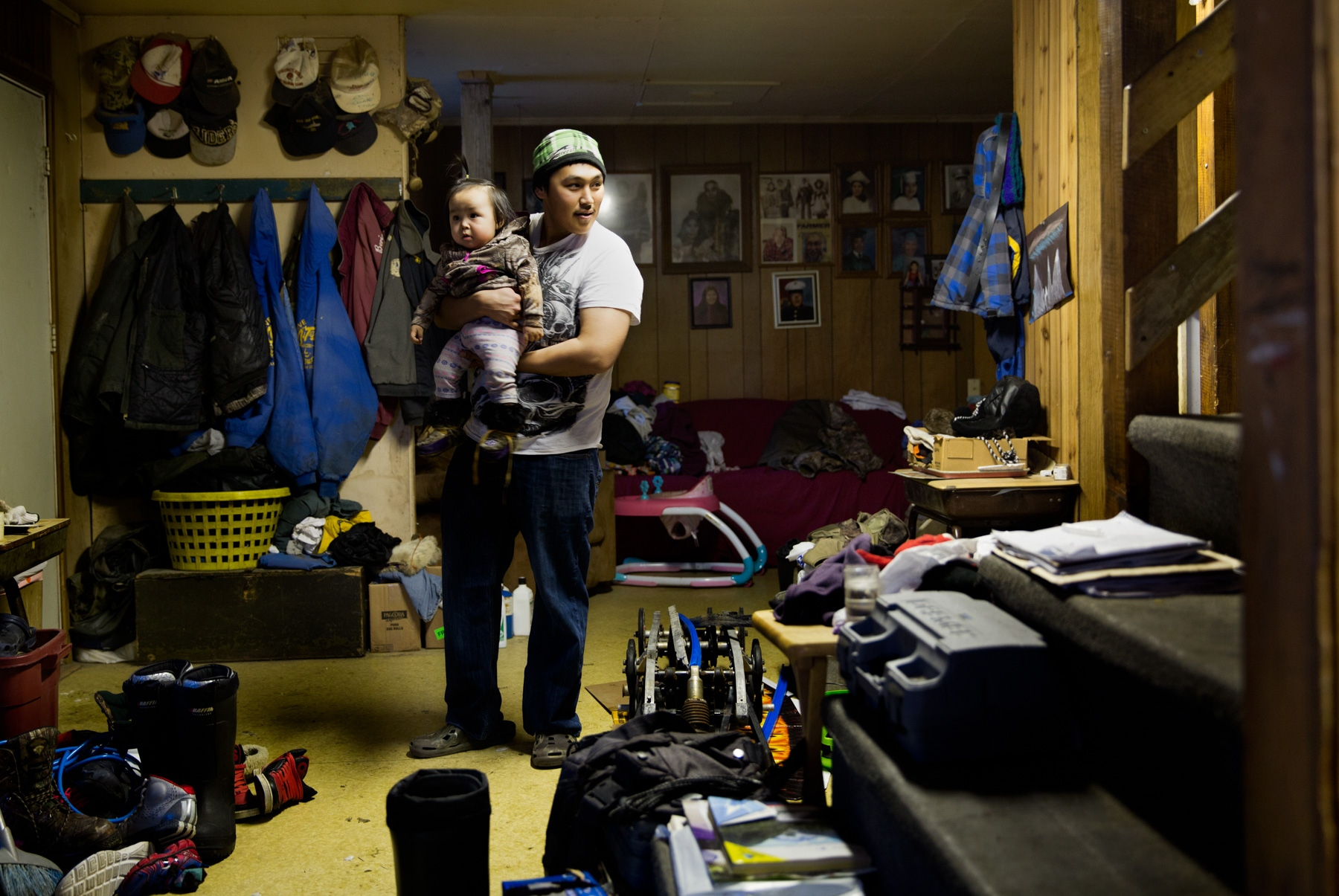 A resident of Shishmaref holds his daughter in their home that he shares with his father. Residents on the island face an uncertain future — it faces inundation because of melting permafrost and the rising water levels resulting from climate change.