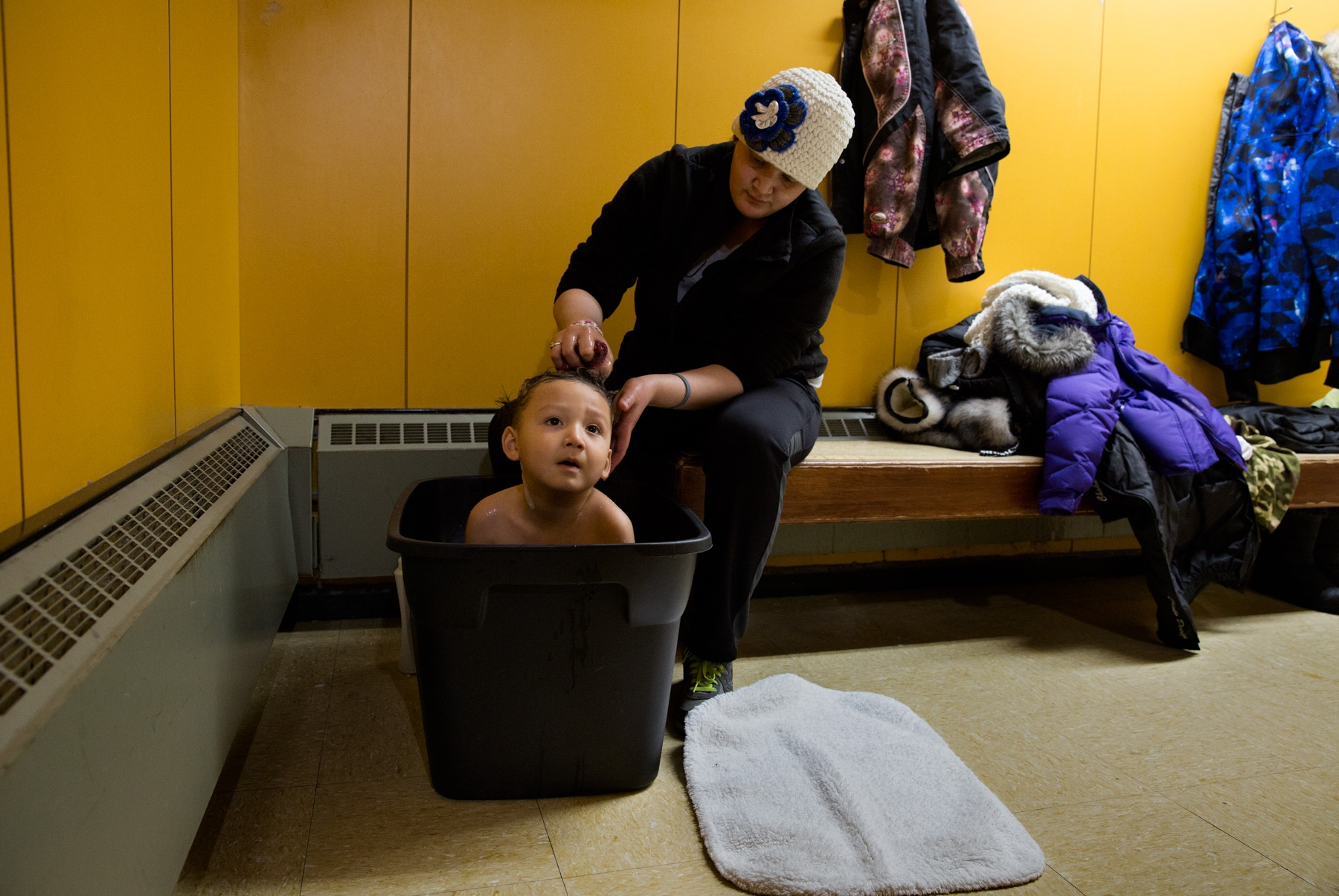 Nora Iyatunguk washes her son, Gilford, in the women's section of the Washeteria in Shishmaref, Alaska. A bucket of hot water for this purpose is $2.00. The Washeteria is the only place for residents to take showers and/or wash their clothes. Elders get their laundry done for free and get free use of the showers.