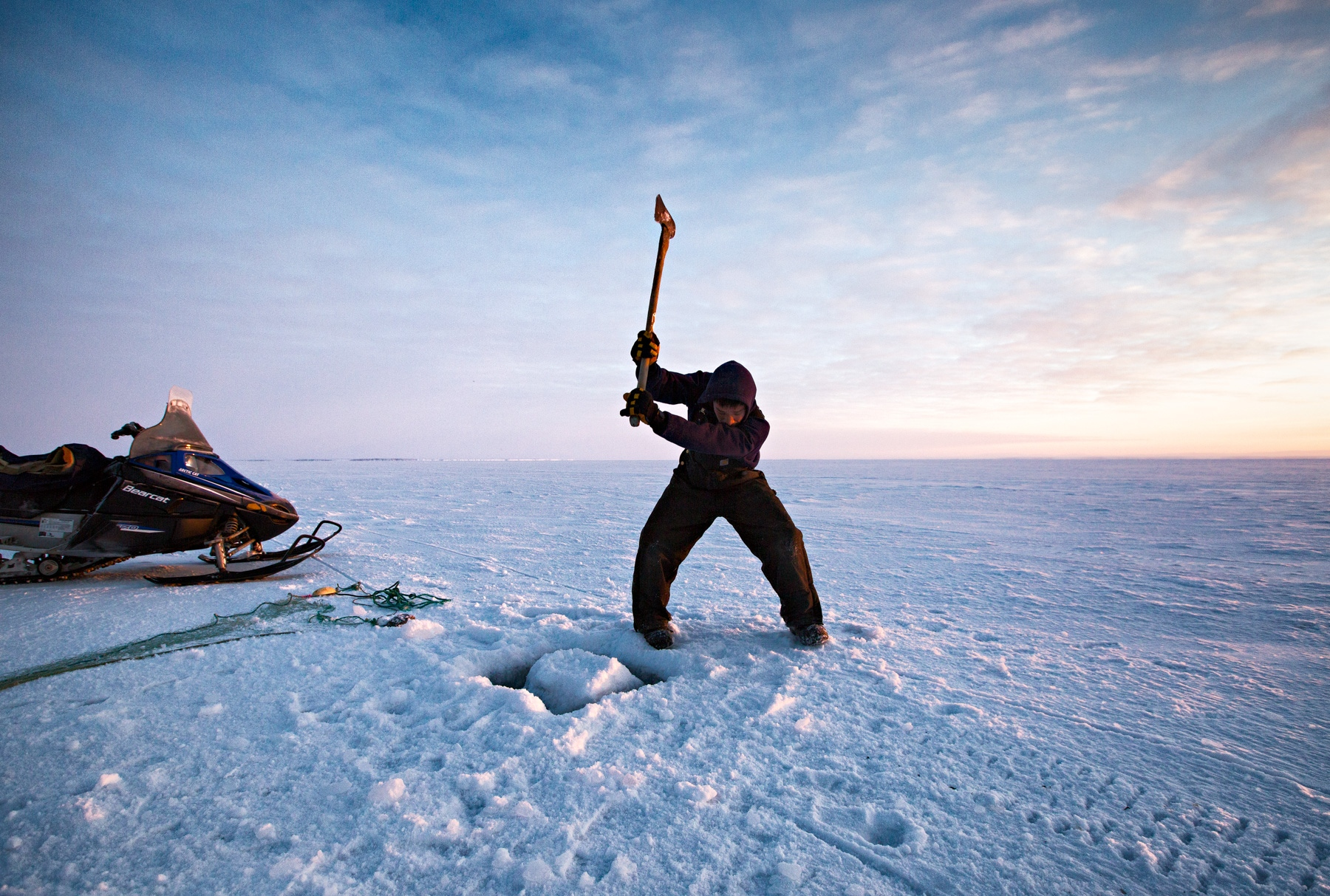Andrew Ningealook, 26 years old and a life long resident of Shishmaref, breaks the ice before laying his fishing net under the ice.