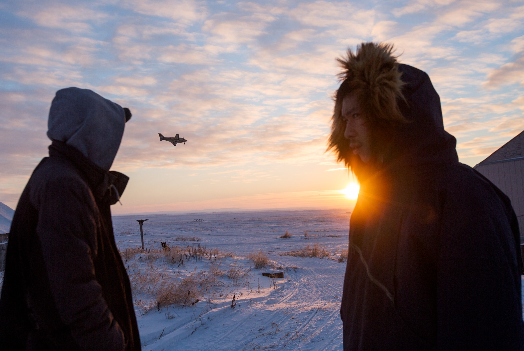 Andrew Ningealook, left, and his cousin Thomas Eningowuk speak together while a twin-engine plane makes its final approach before landing at the Shishmaref airport.