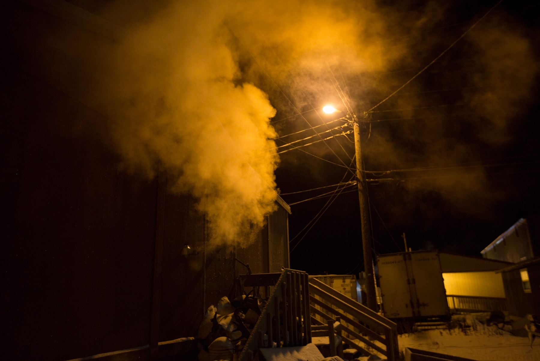 During a frigid night, smoke pours out of the side chimney of a home in Shishmaref, Alaska.