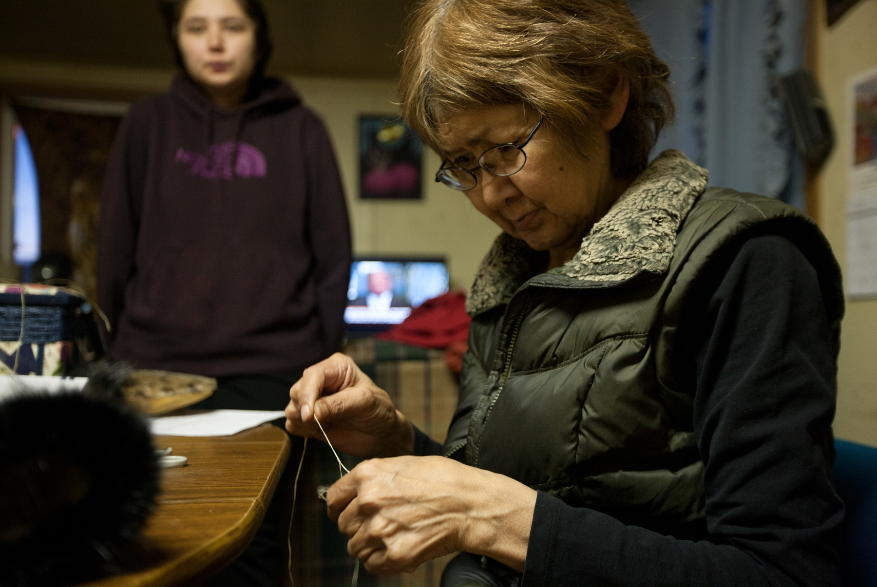 Allison Neyoktok, 26, watches her mother, Catherine Neyoktok, 62, sew mittens using seal fur and skin. On weeknights they play bingo at the Shishmaref Community Center. Catherine is a fourth generation of Neyoktoks born in Shishmaref.