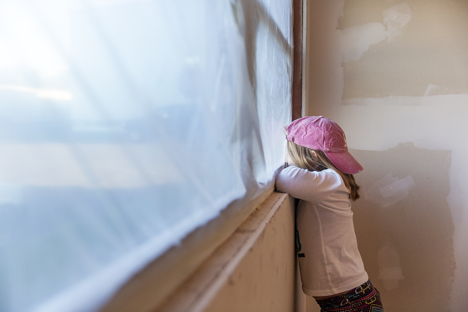 Katherine stands by the window while her mother, Sarah, paints the walls.