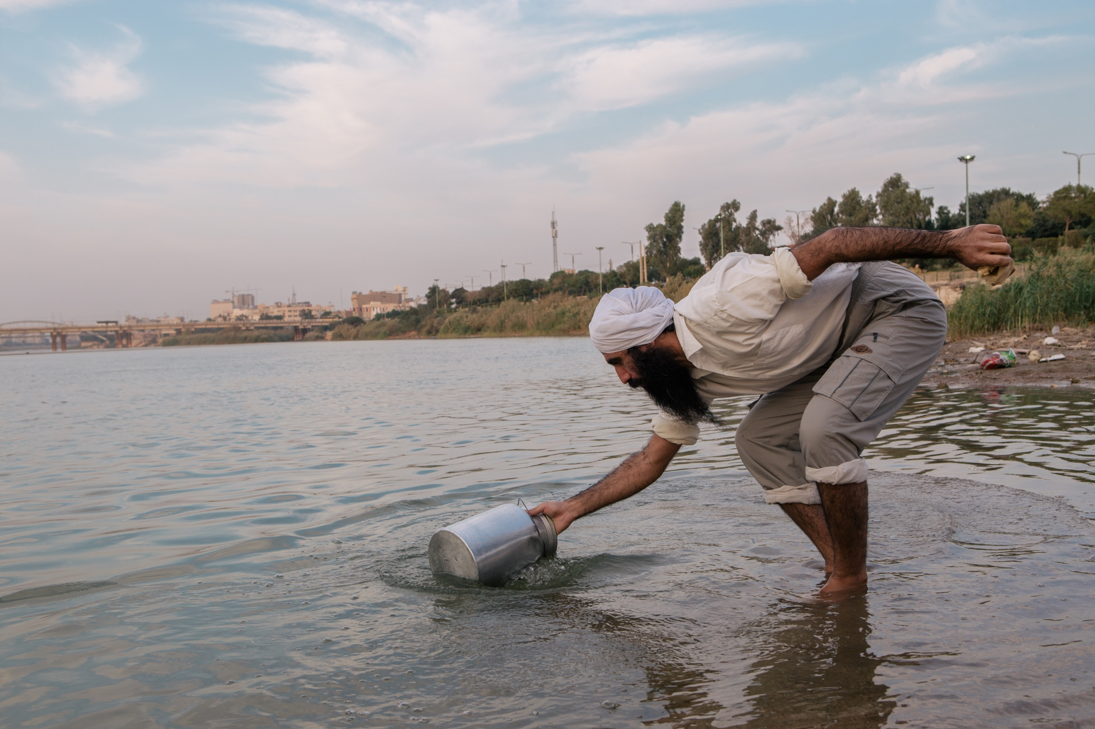 A Tarmida – the second rank of Mandaean priesthood – stands ankle-deep in the water and uses an Aluminum pail to bail the water directly from the river. He will return home and boil the water, not as a means of purifying it, but rather, to separate the sediment. He drinks the water daily.  younger adherents avoid the weekly baptisms and reserve that close interaction with the water for the more significant occasions, like baptism rites after marriage. Siamak, a young Mandaean man, said he had become ill after drinking the water from the river during a religious ceremony.  September 2016