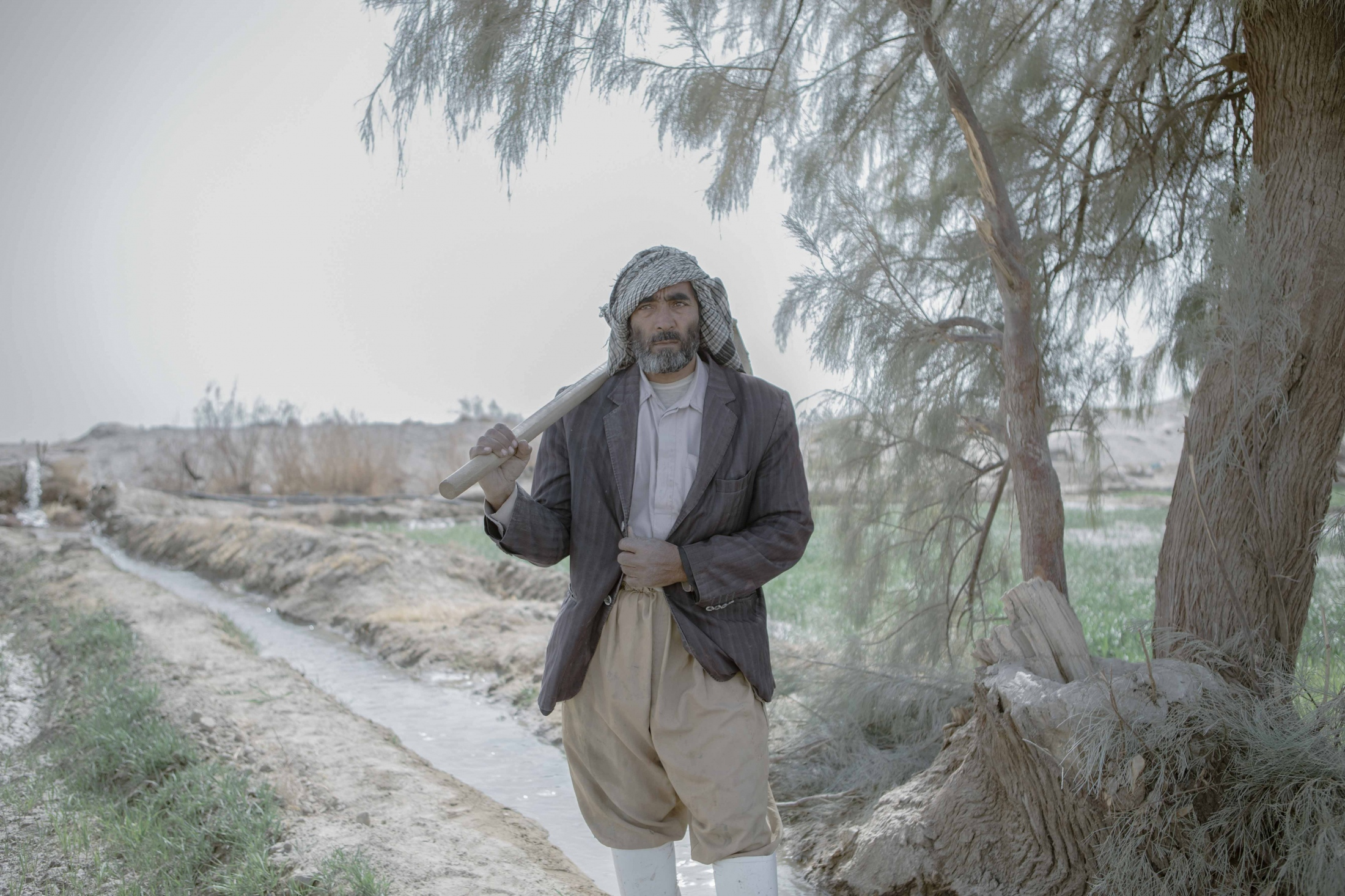 "Mohammed,48, is watering his land from a stream of the Helmand River. He says ""I am lucky that my farmland is next to a stream of the Hirmand river where water sometimes flows from of Afghanistan."" The irony that surrounds Sistan and Balouchestan is that although the region is struck by drought, there is no change in the old irrigation methods and people water their lands using traditional methods. Sistan province.Iran. 2018"