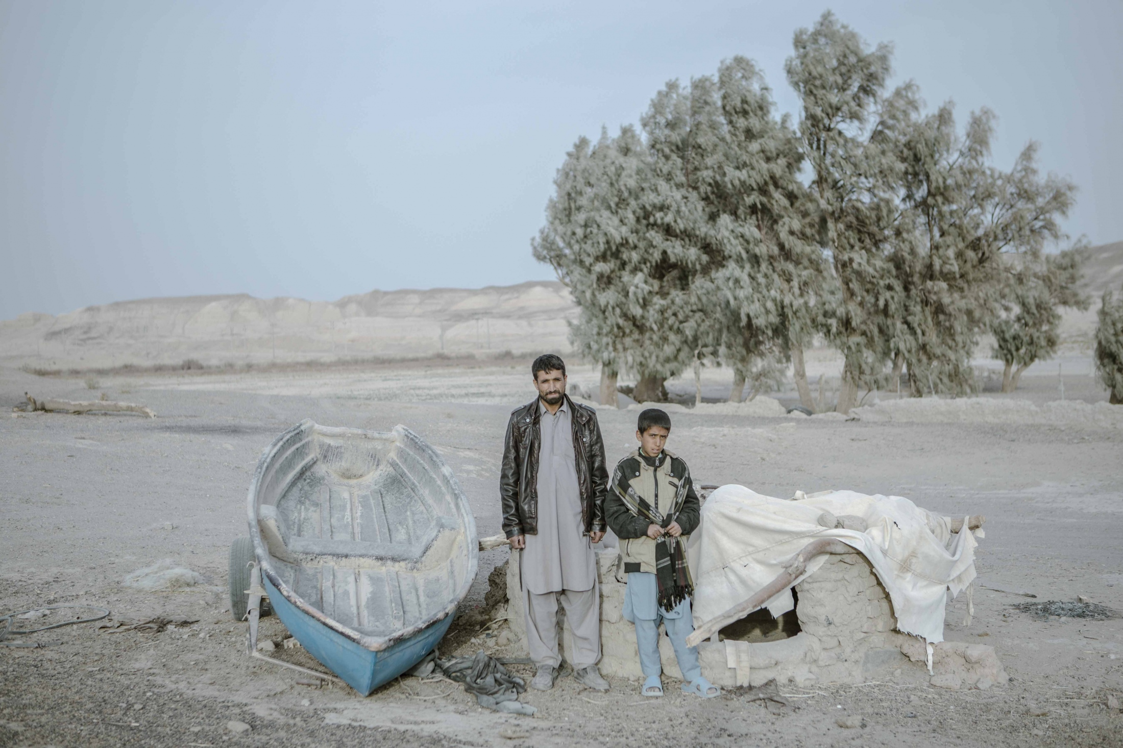 Father and son stand by the boat left in Hamun arid land.40 Mohammed was a farmer and fisherman before dry up of Hamun Lake.now the only job left for him is animal husbandry. After the complete disruption of the water from the Hirmand River in Afghanistan, which led to an increase in the severity of the drought in Iran, the people of the area lost their agricultural activities. The farmlands have now become a wasteland. Also, with the drying up of the Hamun wetlands, fishing in the area, which was one of the indigenous businesses in the area, has completely disappeared. The abandoned boats in this dried-up wetland indicate a very bad and critical situation of the region.Qorqori Rural District.Sistan Province.Iran.2018