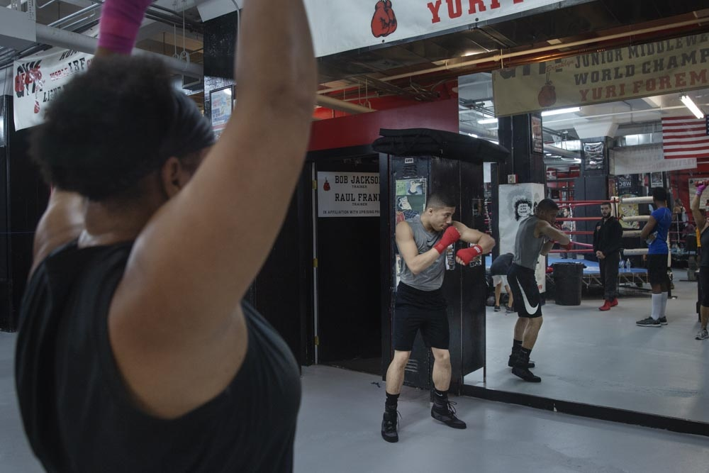 A professional boxer practices in front of the mirror while Yvonne lifts weights.