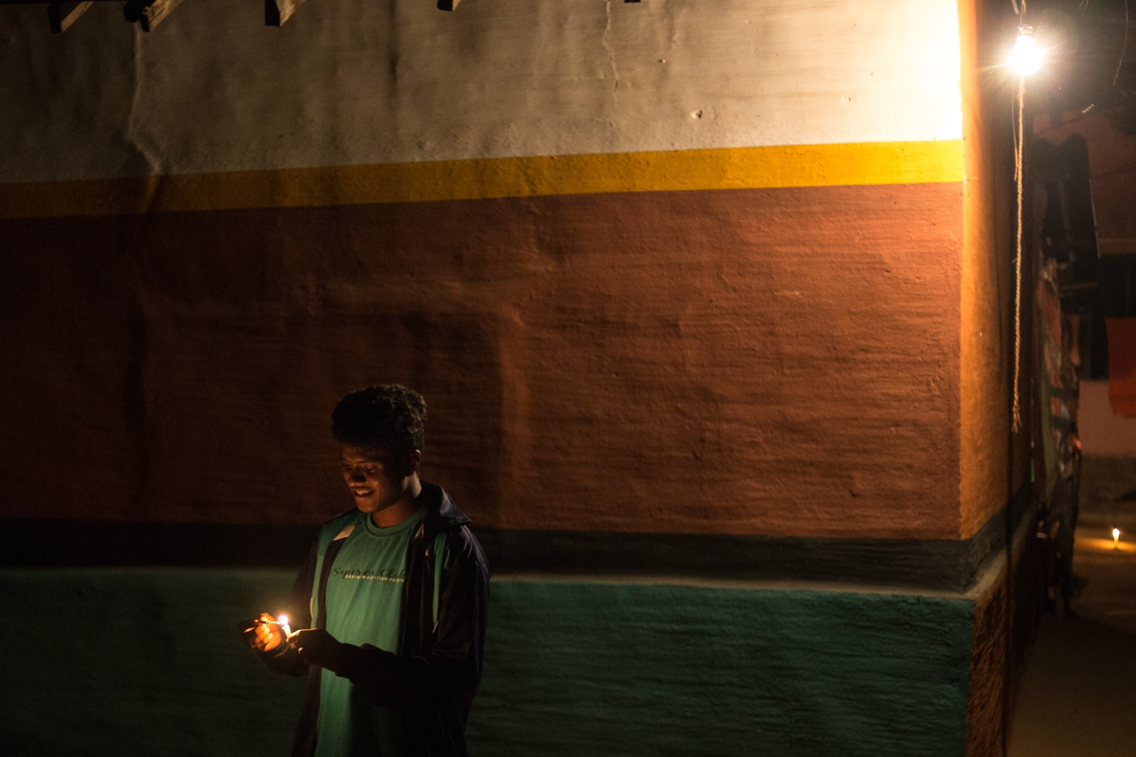 A boy lights a candle during Sohrai, a tribal...