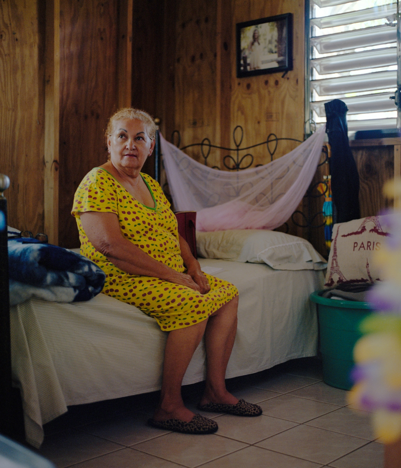 My grandmother, Amparo, sits and reflects in her bedroom after finishing a call with my aunt Giacinia in Florida. During my time visiting after the storm, she would joke how I was leaving New York in 2017 and coming to Puerto Rico in 1950. She told this joke to lighten the spirits due to the lack of power and water in my relatives' homes. Ponce, Puerto Rico, February 2018.
