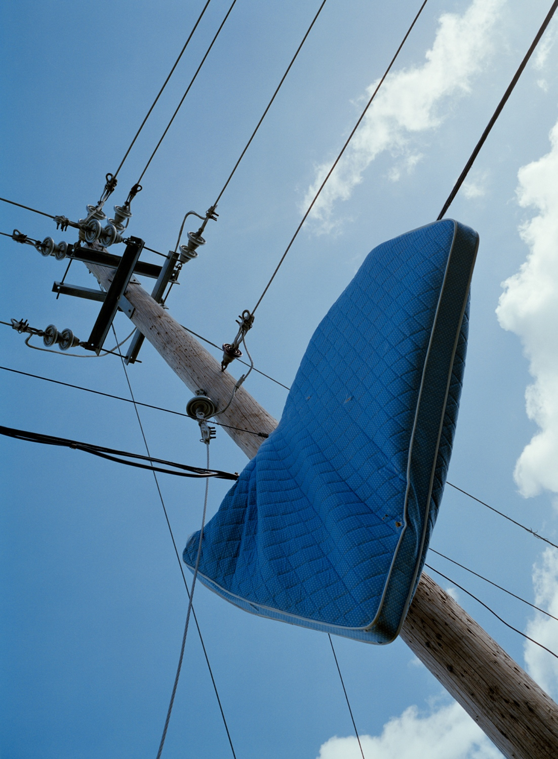 A mattress, blown onto power lines, as a result of the storm's category-five winds, still hangs there three months after Maria made its way through the island. Ponce, Puerto Rico, December 2017.