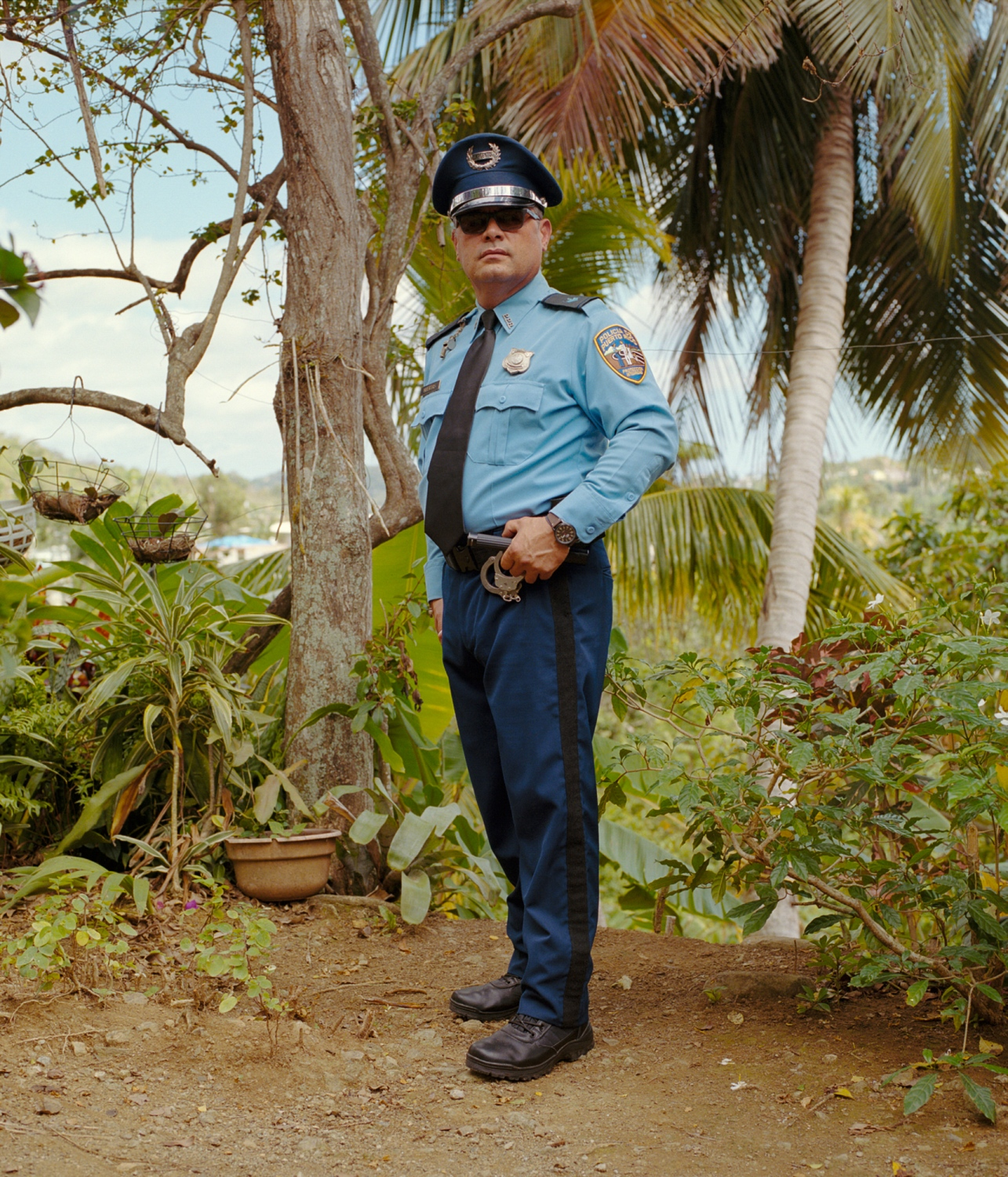 My uncle Luis stands in his Puerto Rico Police Department uniform with the city of Ponce behind him. He has been a police officer on the island for just over 31 years. Over lunch, he spoke about his fear of a crime wave after the blackouts hit the island, last year after the storm. Ponce, Puerto Rico, February 2018.