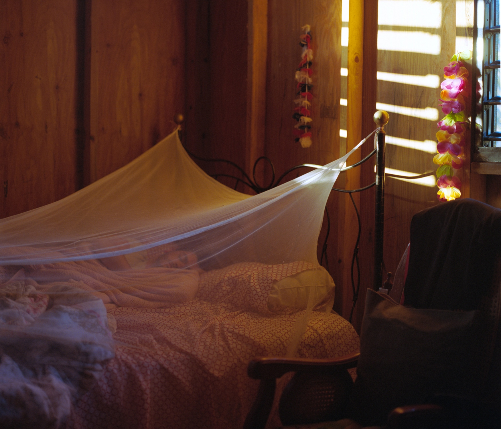 "My brother, Erik, lays under a mosquito net (""mosquitera"") at my grandmother Amparo and Carmelo's home in the barrio La Yuca. After the storm, the use of these nets became even more prevalent with the rise in cases of dengue, a mosquito-borne disease. Ponce, Puerto Rico, February 2018."