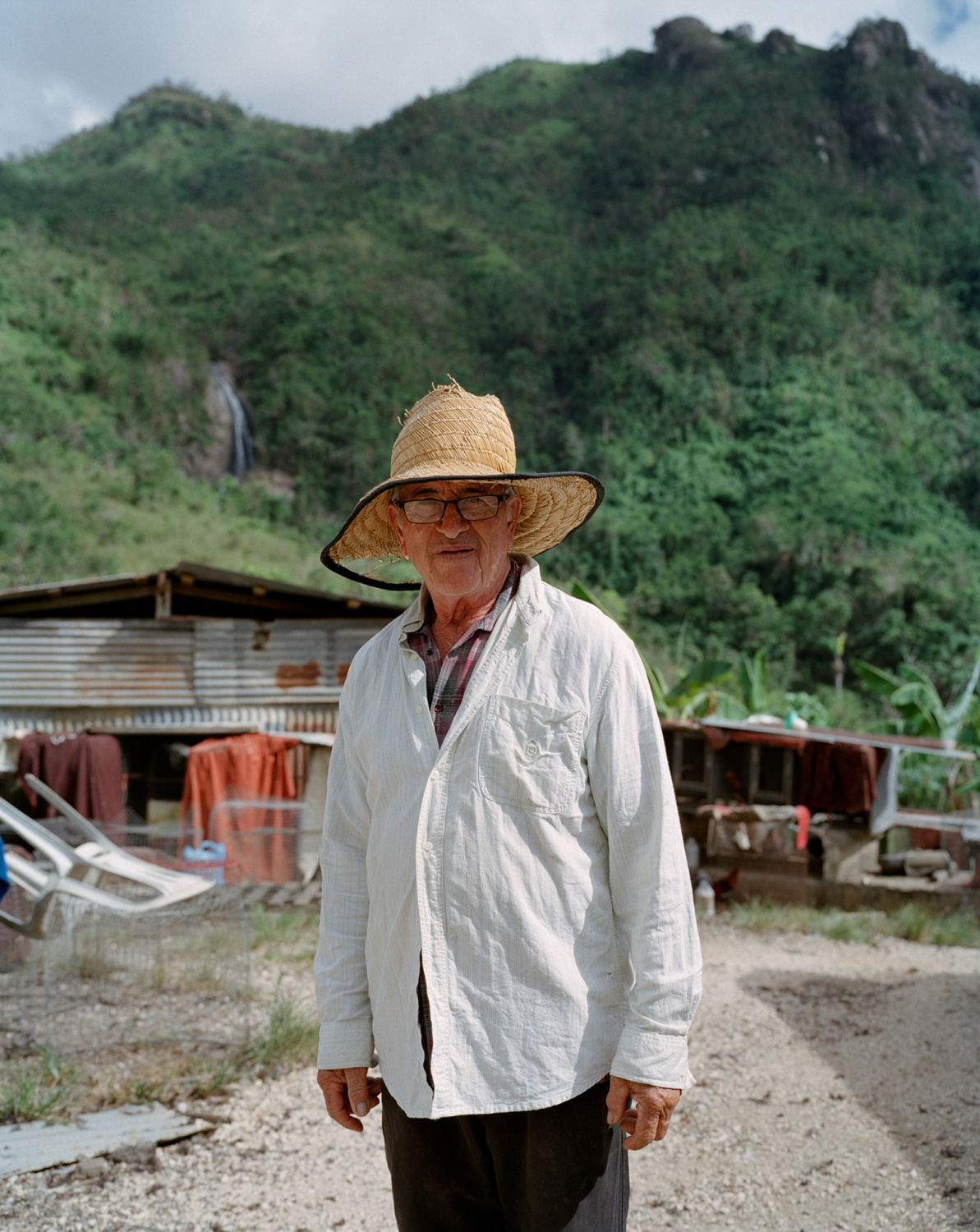 Ñingo Marrero, my grandfather Horacio's cousin, stands for a portrait in the barrio of Dajao. After the storm, he and many others bathed in the waterfall and river behind the property until the water was restored to their homes. When I was a child, my grandfather would take us on hikes around the barrio and tell us tales about the chupacabra, which he claimed killed his roosters, and how it lived in these woods. Villalba, Puerto Rico, December 2017.