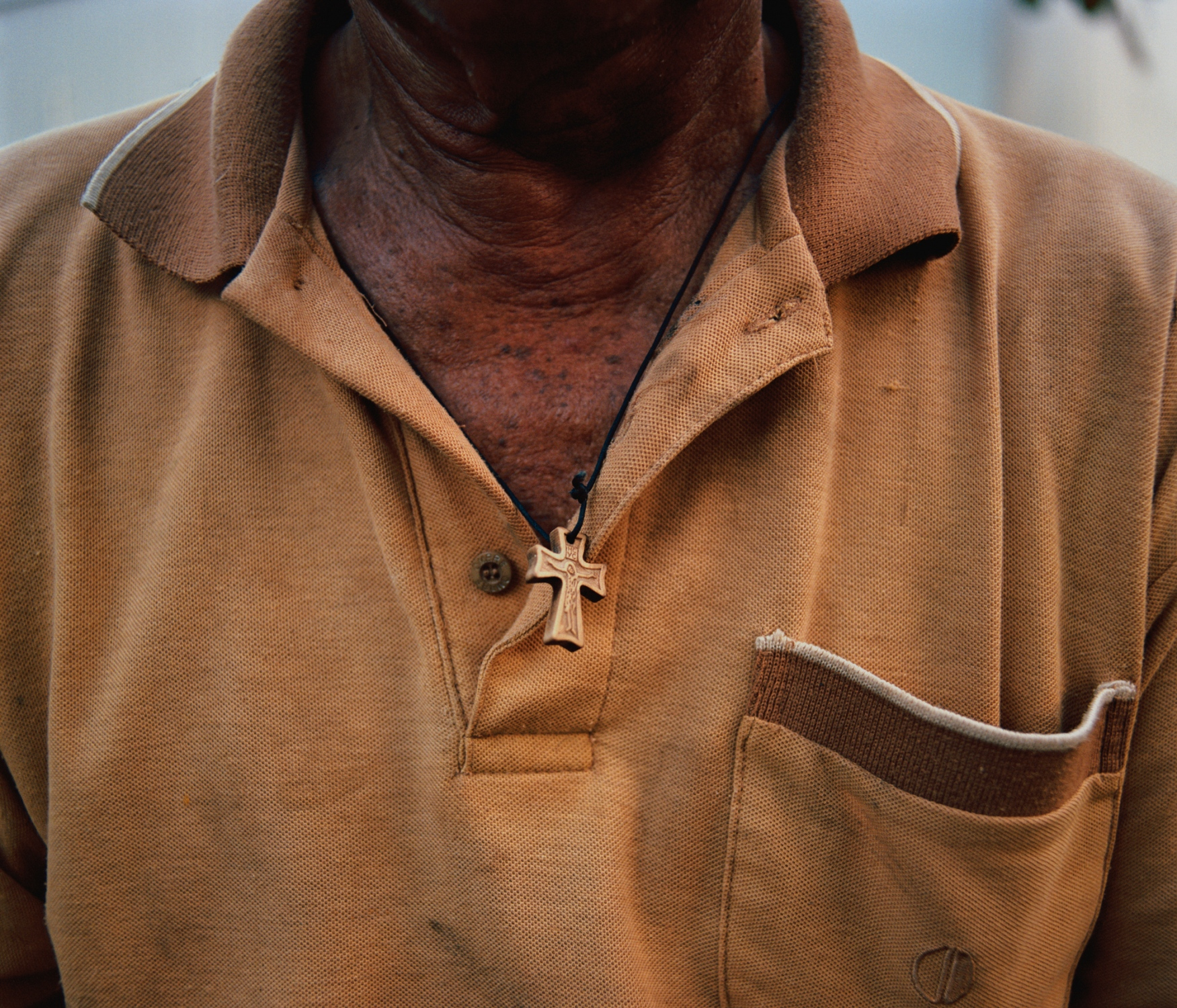 My grandfather Horacio's daily attire- his necklace, with a wooden cross, and a collared shirt - that he wears to perform the daily errands around the property, soaks up the colors of the early morning sunrise. Villalba, Puerto Rico, July 2018.