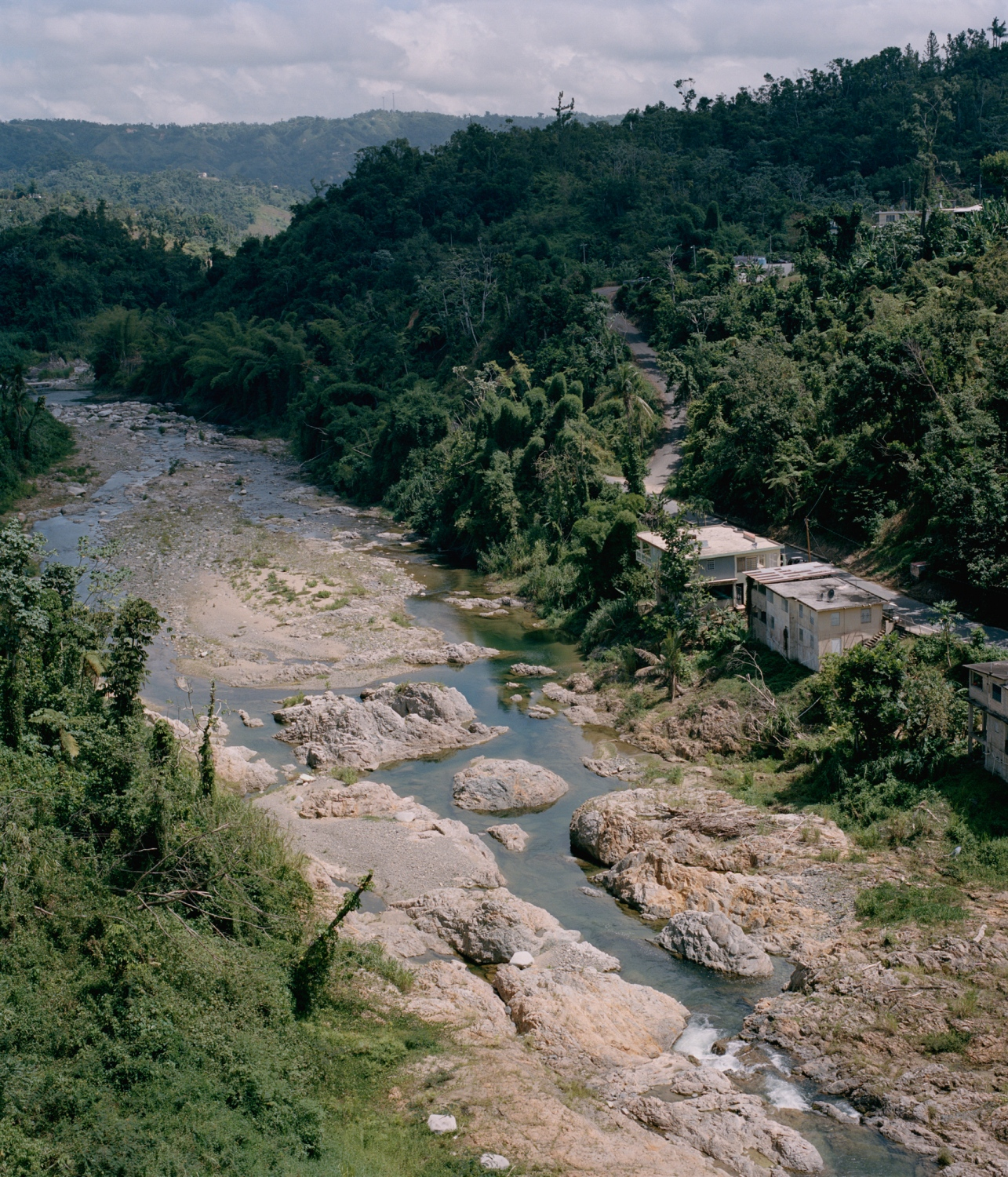 The Pelleja River flows alongside the barrio Arenas in Utuado ten months after the storm, with much of the vegetation having grown back.  Utuado, Puerto Rico, July 2018.