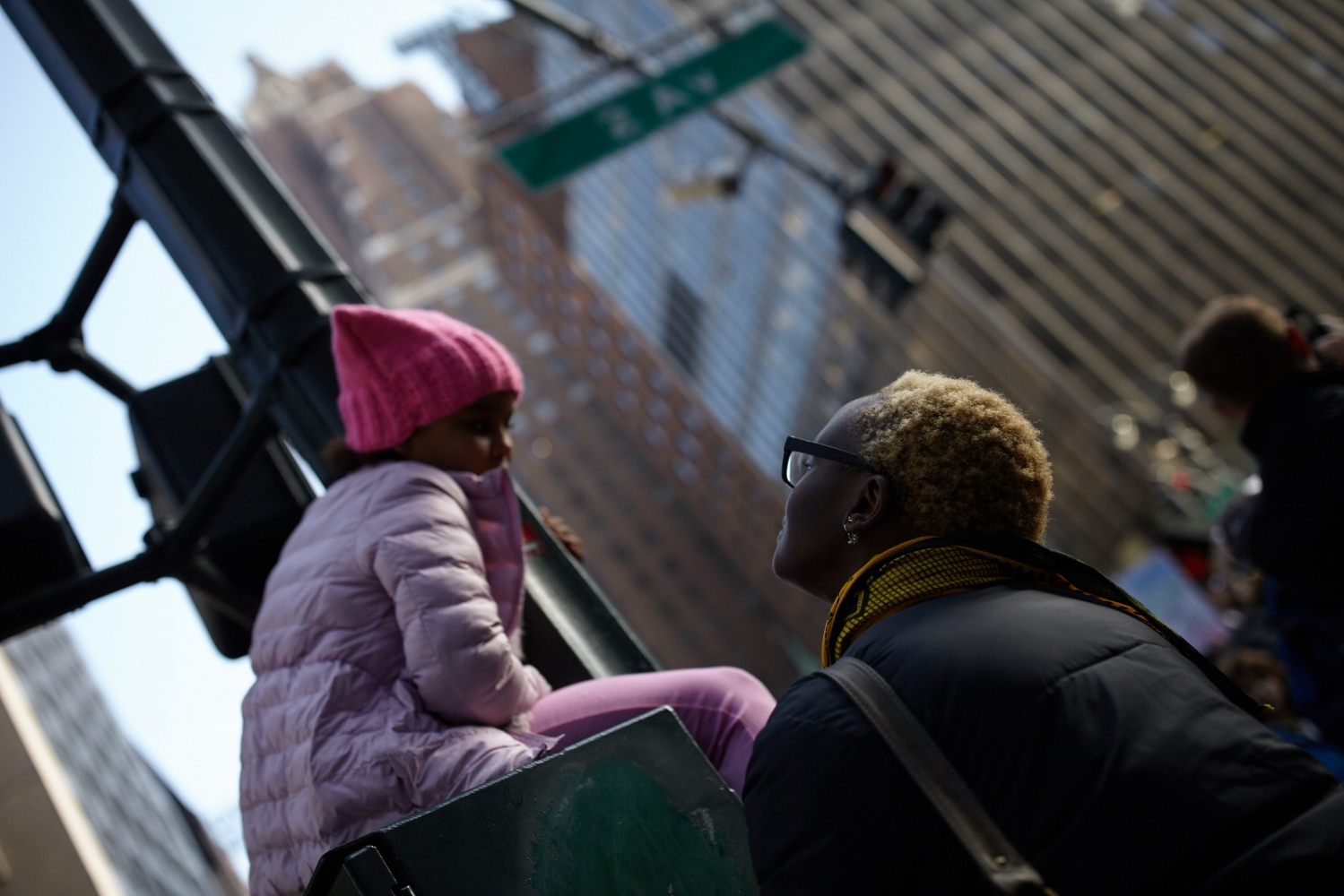A child sits atop a traffic box and speaks to her mother near Dag Hammarskjold Plaza in Manhattan, New York, U.S. January 21, 2017.