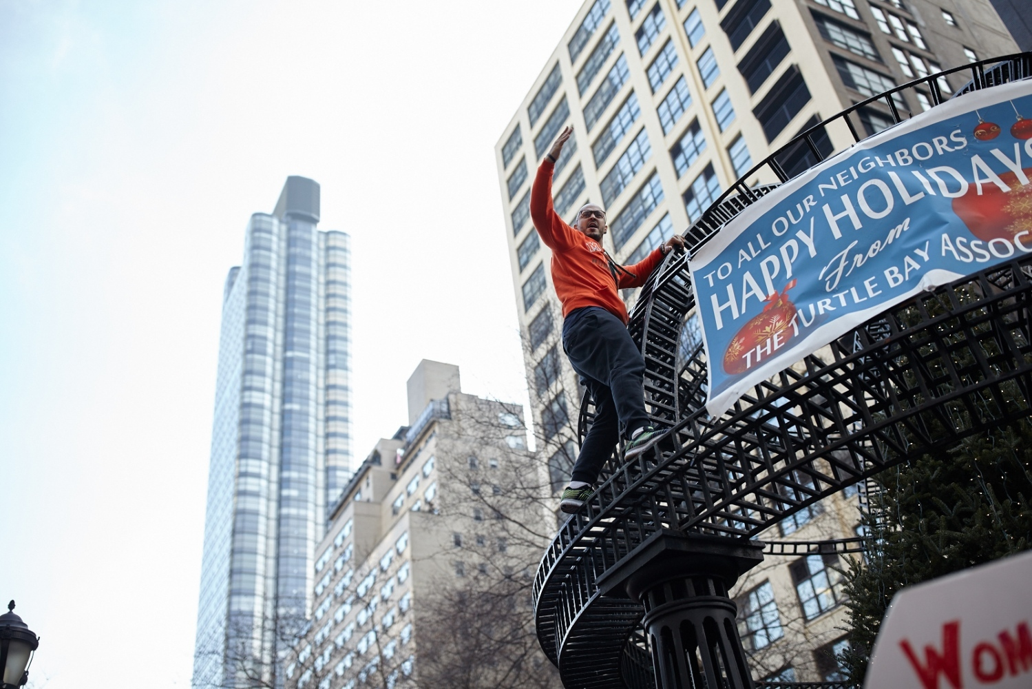 A demonstrator climbs up a metal sculpture and attempts to excite the crowd at Dag Hammarskjold Plaza in Manhattan, New York, U.S. January 21, 2017.