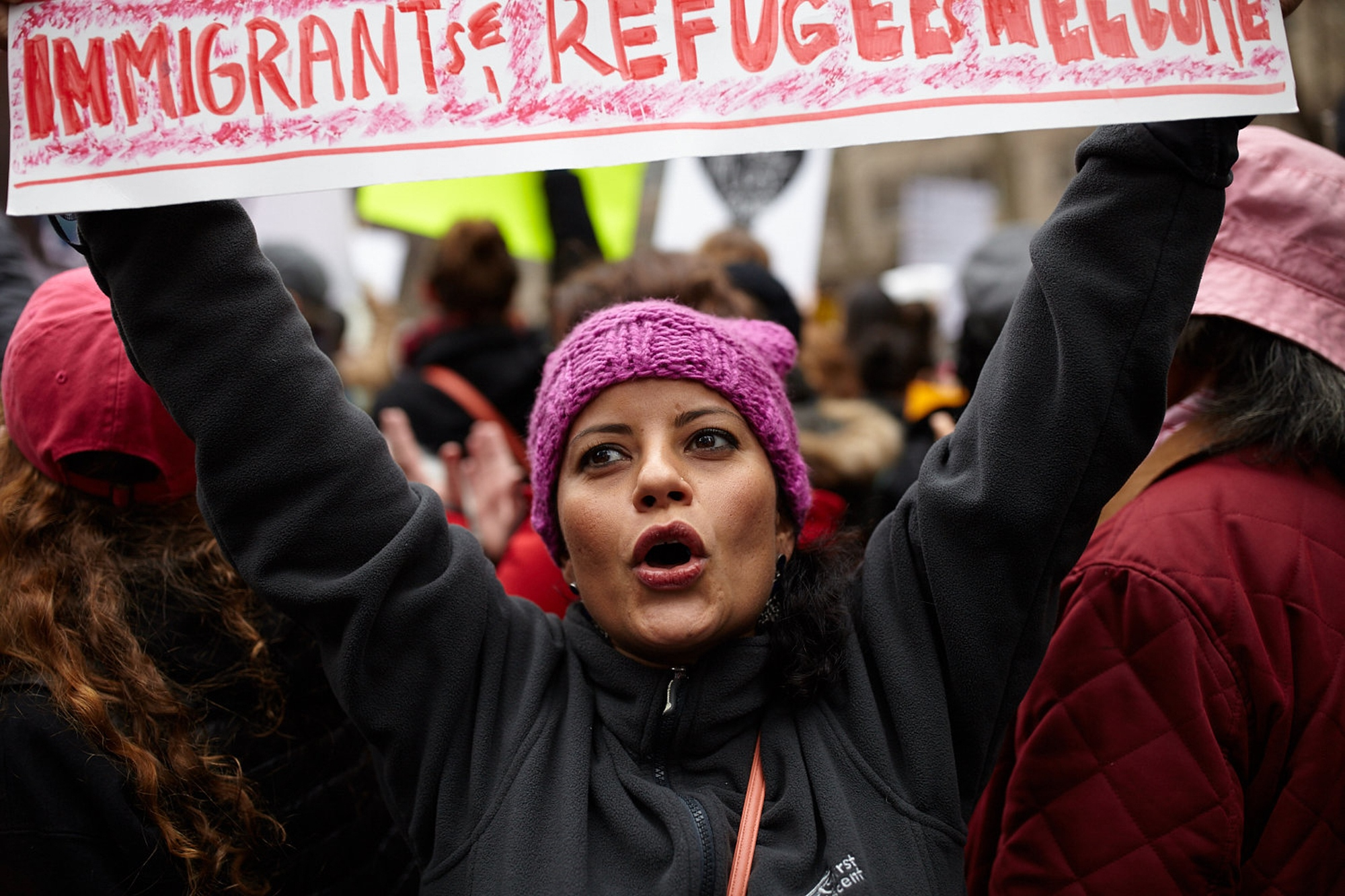 "A demonstrator wears a Pink ""pussy hat"" and holds up a sign that displays the words ""Immigrants and Refugees Welcome"" at Dag Hammarskjold Plaza in Manhattan, New York, U.S. January 21, 2017."