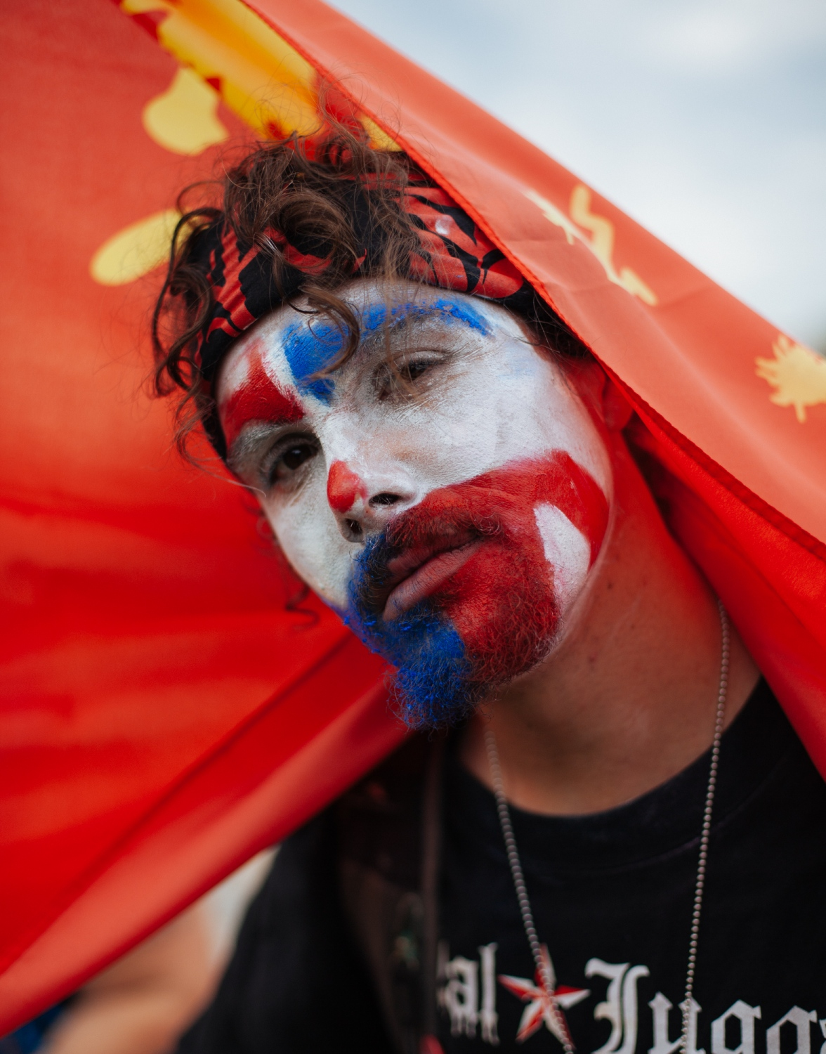 A male in Juggalo face paint drapes himself with a red flag that displays an orange hatchet man logo at the Juggalo March Juggalo March at the National Mall, Washington, D.C., U.S. September 16, 2017.