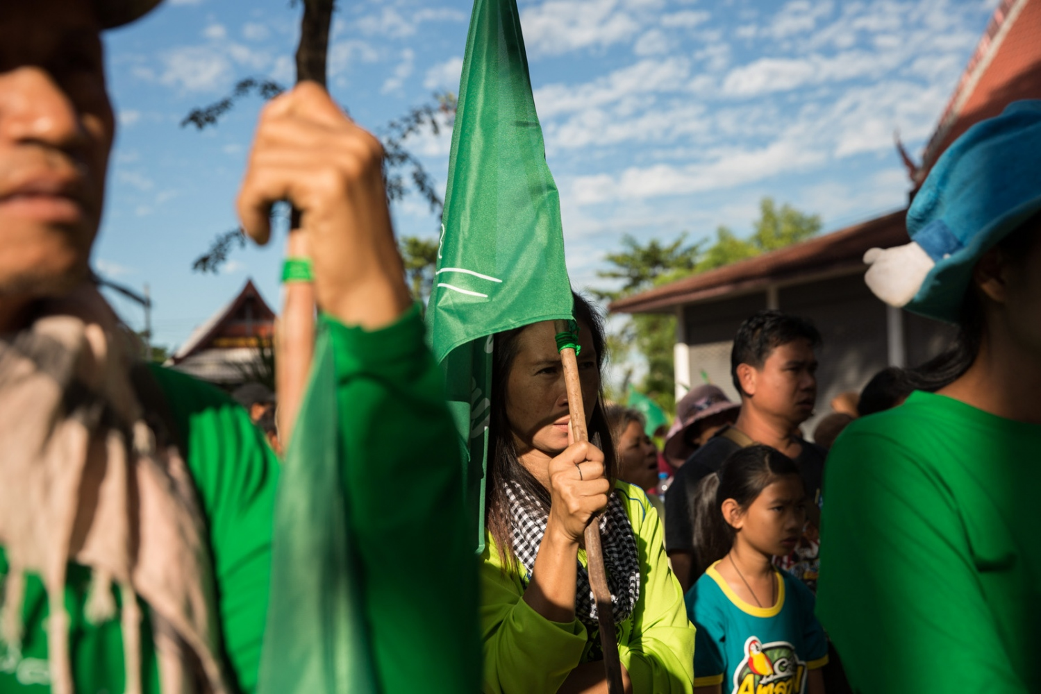 A women protestor uses her anti-mining flag to hide from the sun. On the morning of the first day approximately 200 locals gathered at a local temple in Wanon Niwat district ready to begin their walk to the provincial capital.