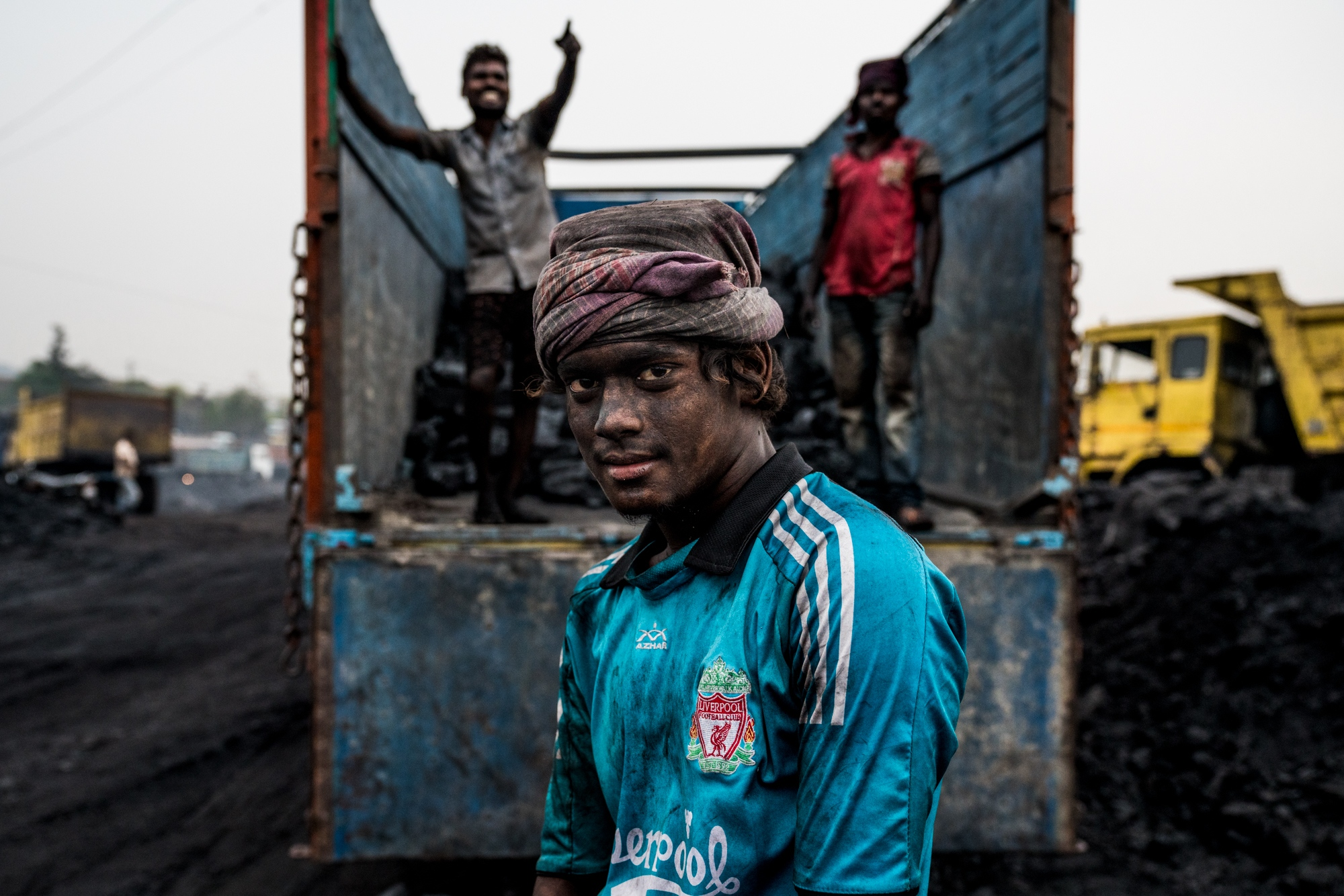Portrait of a miner loading up coal on to a transport truck that will take the coal away to power India's megacities.