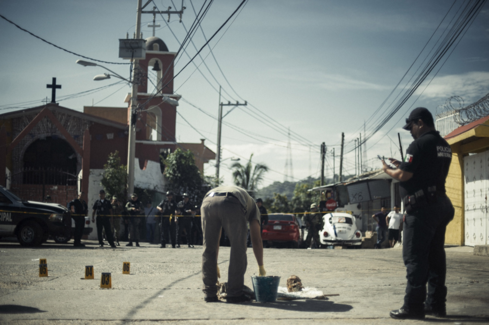 Mexican soldiers and police guard a severed head which was left as a message between cartel members in the colonia primero de mayo neighborhood, which is one of the many neighborhoods which has found itself in the center of Mexico's long drug war.  The severed head had been dissolved in acid not as a means to hide, evidence but to layer an addiional level of depravity to the message being sent.