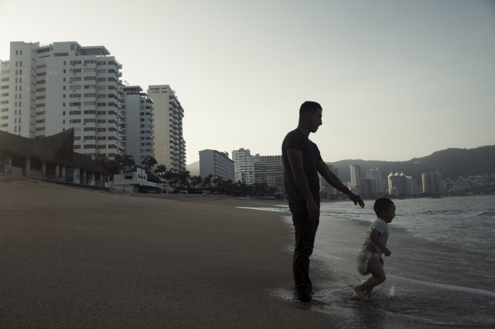 Andres Vladimir, who was visiting Acapulco from Mexico City, introduces his 3-year-old son Harek to the sea.  Many of those visiting Acapulco's shores, especially those with extensive tattooing that could be associated with gang affiliation like Andres, visit the shores in the early hours of the day to avoid possible confrontations which could arise at other times.  A safer time, at dawn Andres didn't have to worry as much about murder.