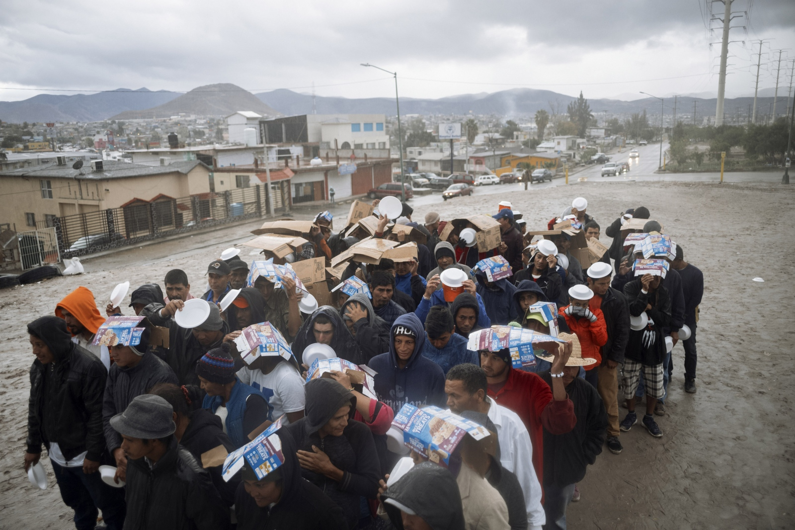 Asylum seekers that have trekked thousands of miles across Latin America fleeing violence and extreme poverty wait in the rain for bean soup provided by Refugio Esperanza Church, outside of barretal, a refugee camp on the outskirts of Tijuana, Mexico where thousands of people wait in limbo.