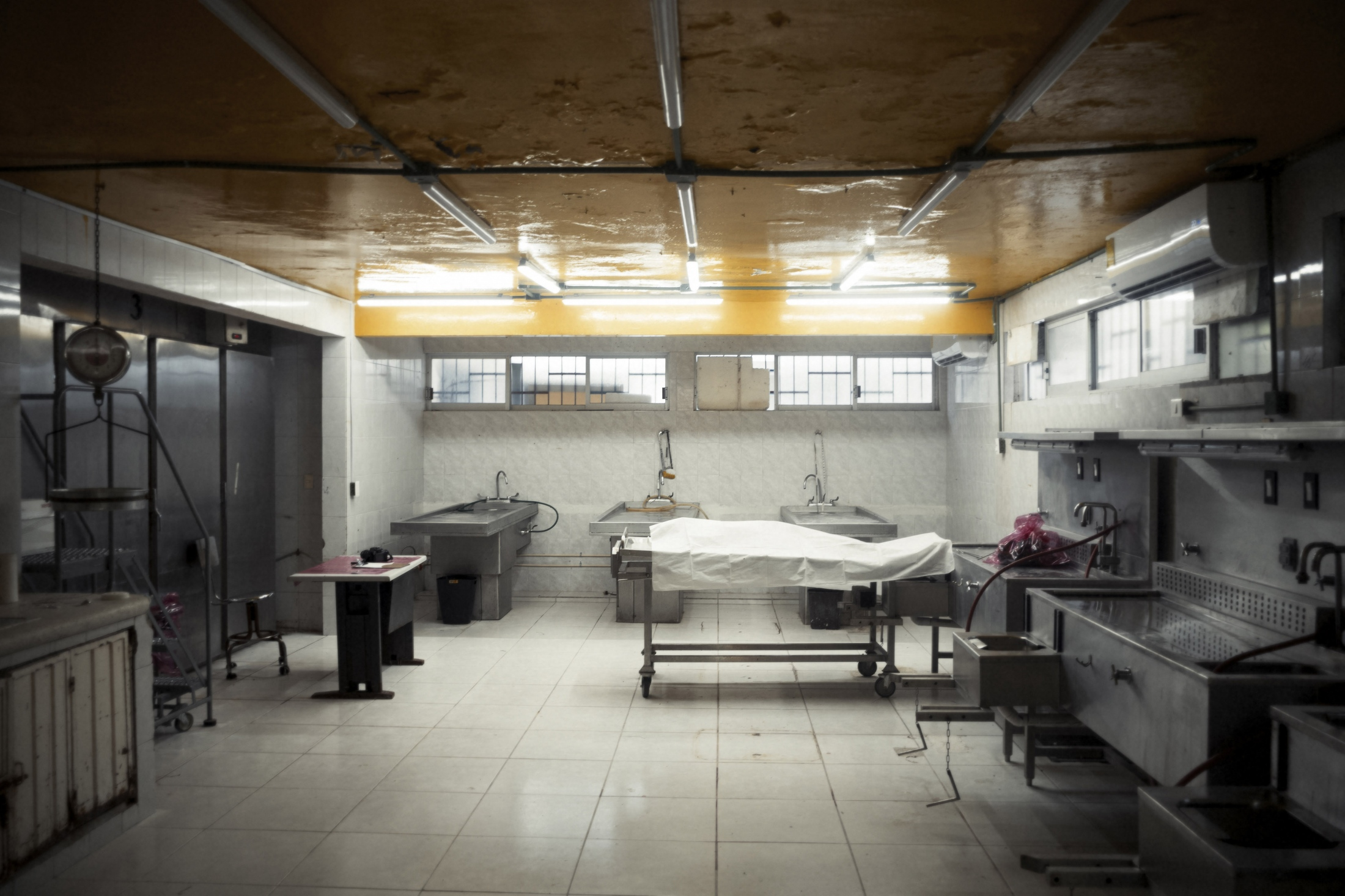 The forensic medical services morgue in Acapulco is often full to capacity, even though it has 5 refrigerators, which can hold approximately 400 bodies at a time.  A murder victim, recently found in a dry riverbed nearby, awaits autopsy at the morgue.