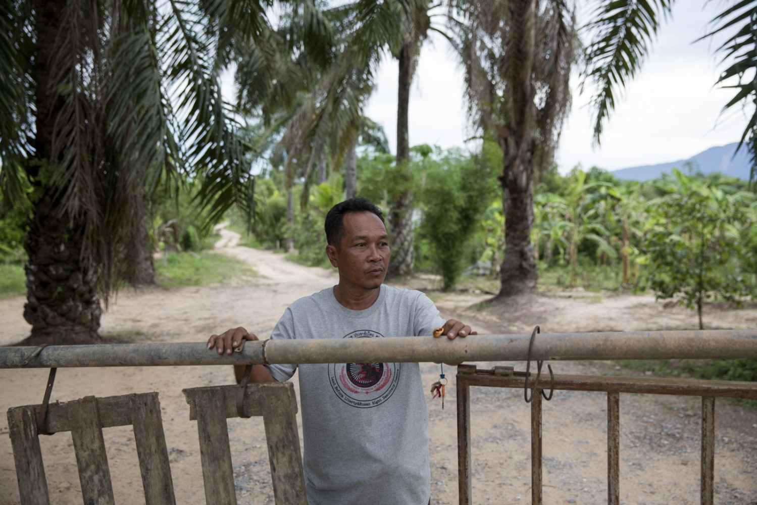 Tawat Ruangsi, 48, stands at the main entrance and security post to Klong Sai Pattana village after having just closed the gate at 6pm. The village tries to limit the number of vehicles entering and leaving during the night and re-opens at 6am. In total the village has 4 security posts which are manned 24 hours a day by the villagers who take it in turn in small groups of 3-4 people. May 2016.