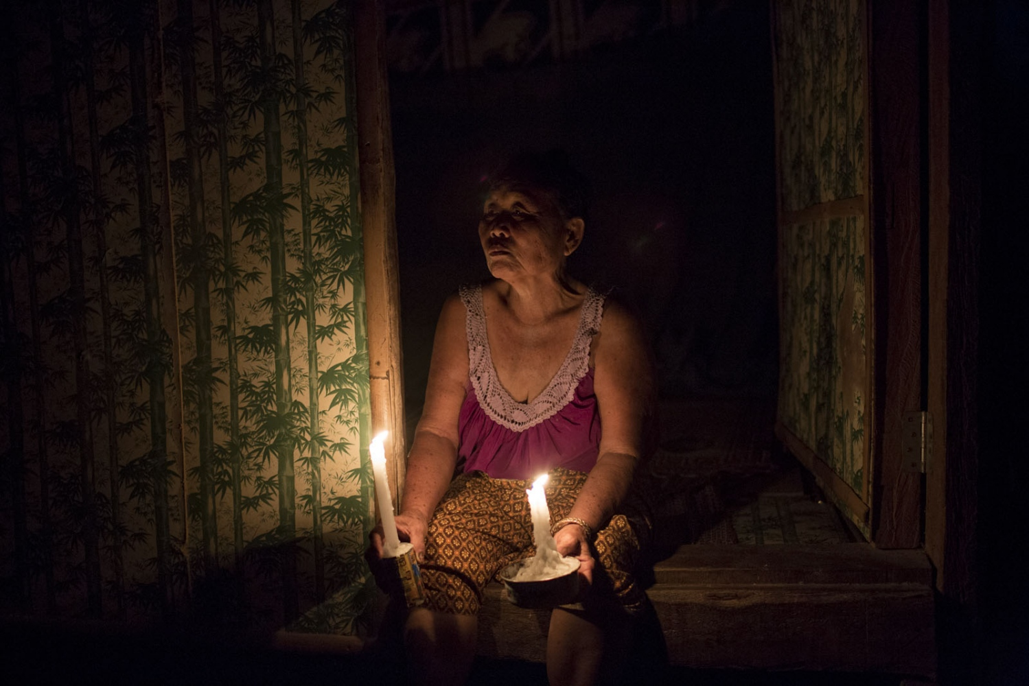 Rattana Seli, 66, sits in the entrance to her hut holding two candles. The village has no electricity so at night mostly candles are used. May 2016.