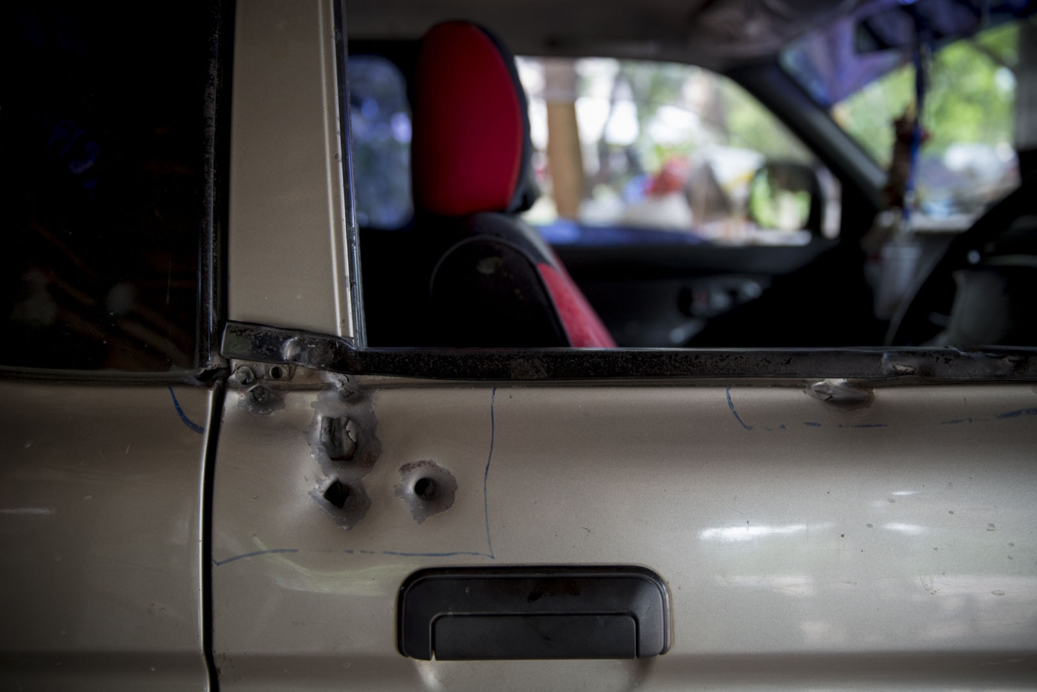 The bullet holes in the side of Supot Kansong's pickup truck where he was shot at close range but survived. May 2016.