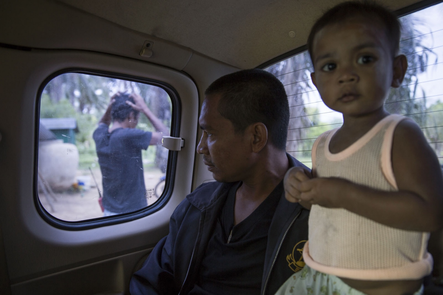Supot Kalasong, 42, leaves the village in a pickup to travel to Bangkok to submit a document to a government office. In April 2016 Mr Kansong was shot in 6 places by an assassin who had been waiting for him to drive past as he returned to the village. He remarkably survived but has since left the community leaving his son and wife. May 2016.