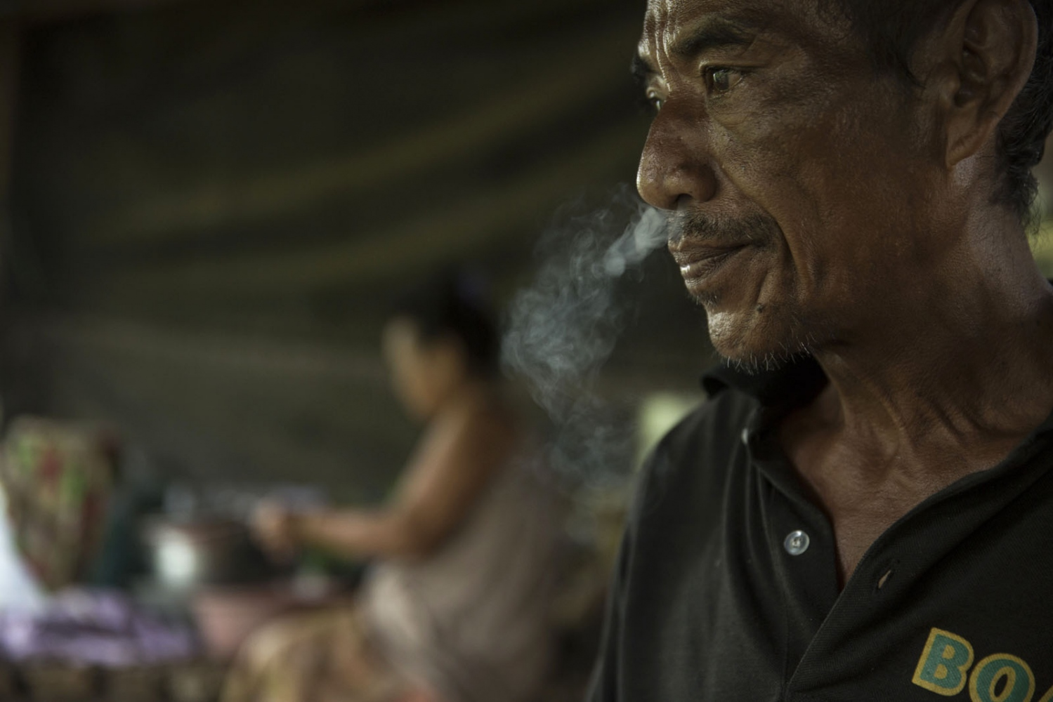 Sukon Dongwun, 54, smokes a cigarette in a neighbours house. May 2016.
